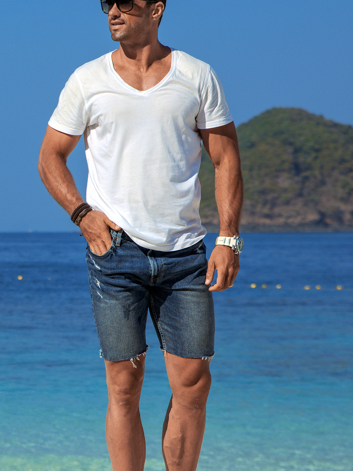 Men's outfit idea for 2021 with white v-neck t-shirt, blue denim shorts. Suitable for summer.