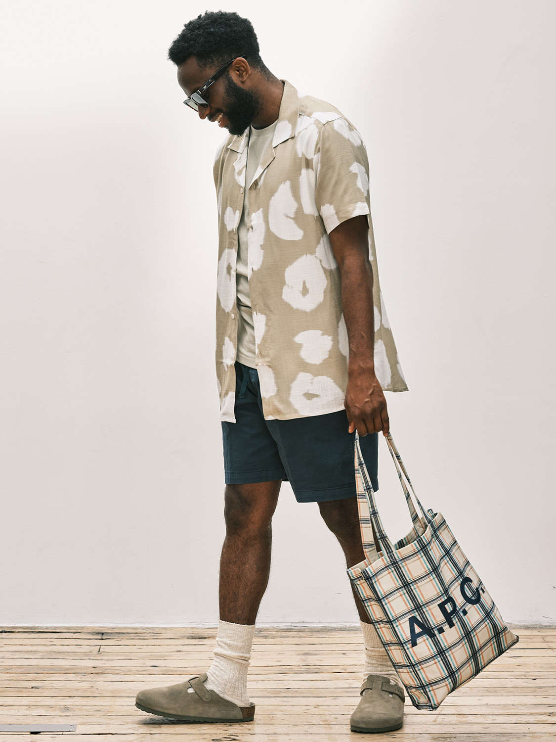 Men's outfit idea for 2021 with neutral short-sleeved patterned shirt, neutral plain crew neck t-shirt, navy shorts, neutral tote bag, neutral sandals. Suitable for summer.