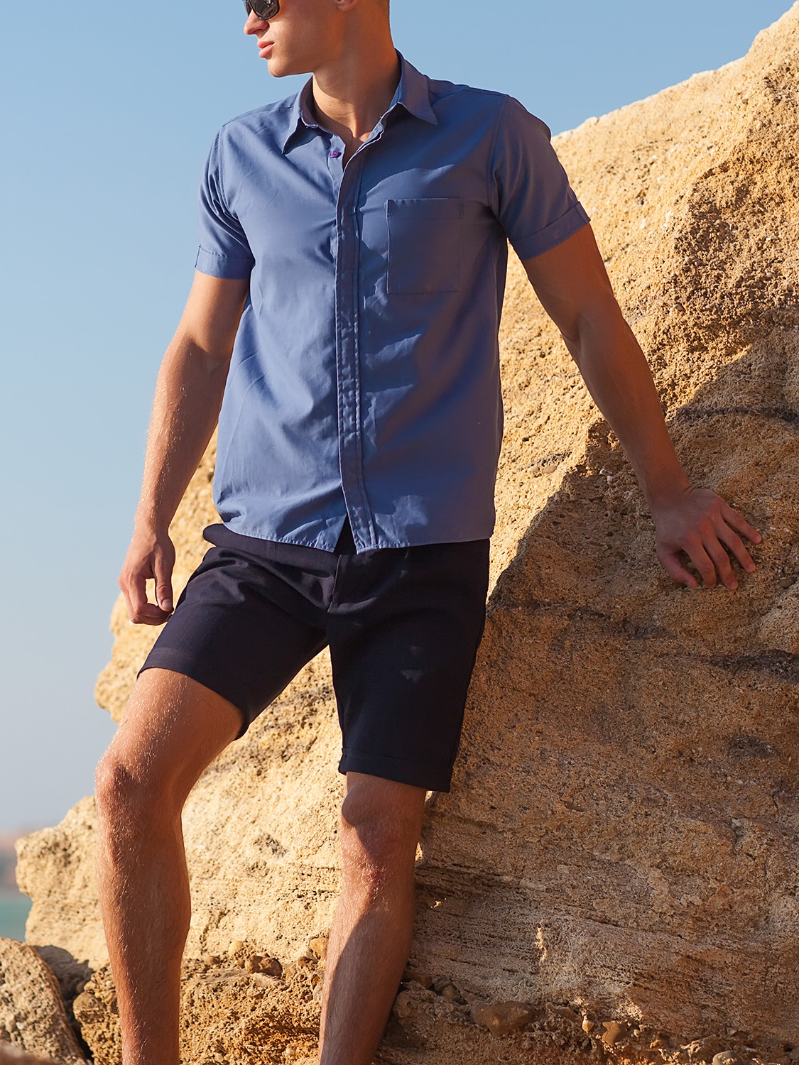 Men's outfit idea for 2021 with blue short-sleeved plain shirt, navy cotton shorts, black sunglasses. Suitable for spring and summer.