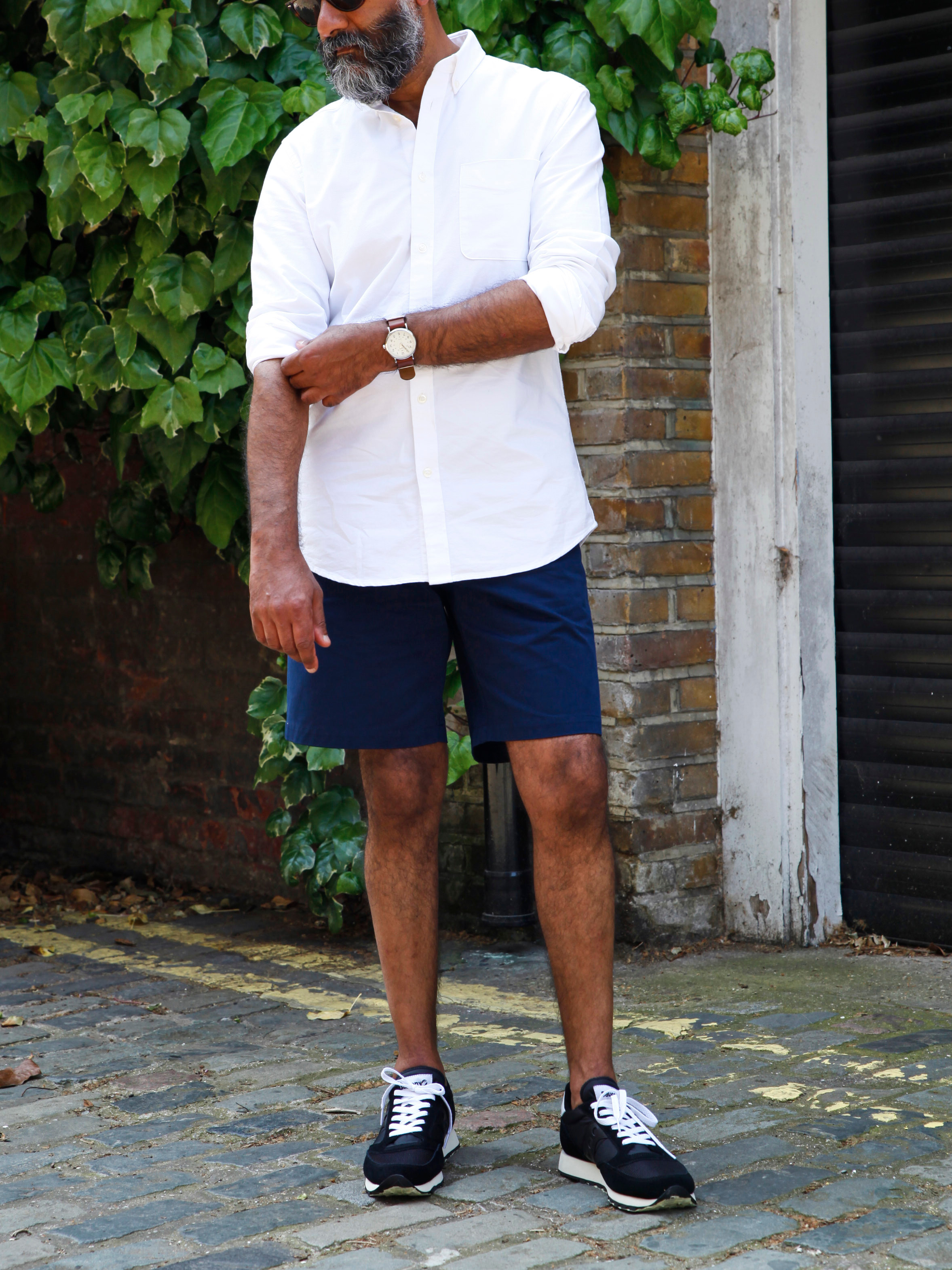 Men's outfit idea for 2021 with white casual shirt, navy shorts, leather strap watch, neutral trainers. Suitable for spring and summer.