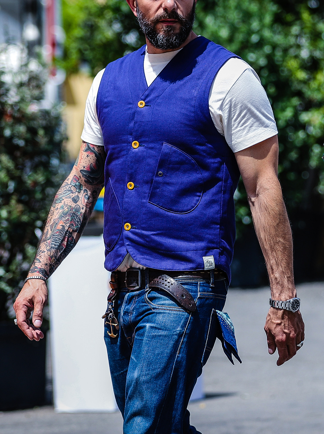Men's outfit idea for 2021 with blue plain waistcoat, white crew neck t-shirt, blue jeans, brown chelsea boots. Suitable for spring, summer and autumn.