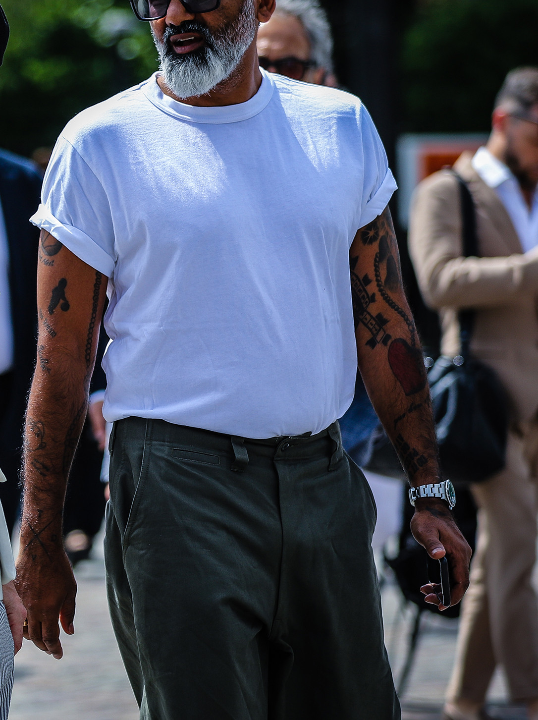 Men's outfit idea for 2021 with white crew neck t-shirt, green chinos, black sandals. Suitable for summer.