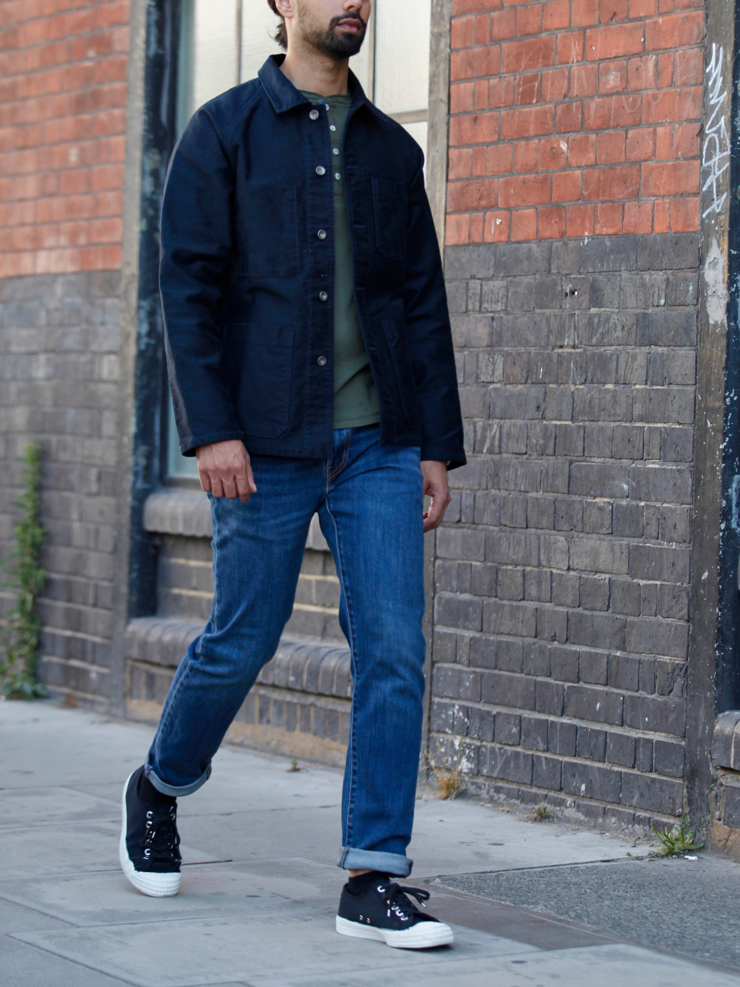 Men's outfit idea for 2021 with utility jacket, long-sleeved henley top, dark blue jeans, black sneakers. Suitable for spring and fall.