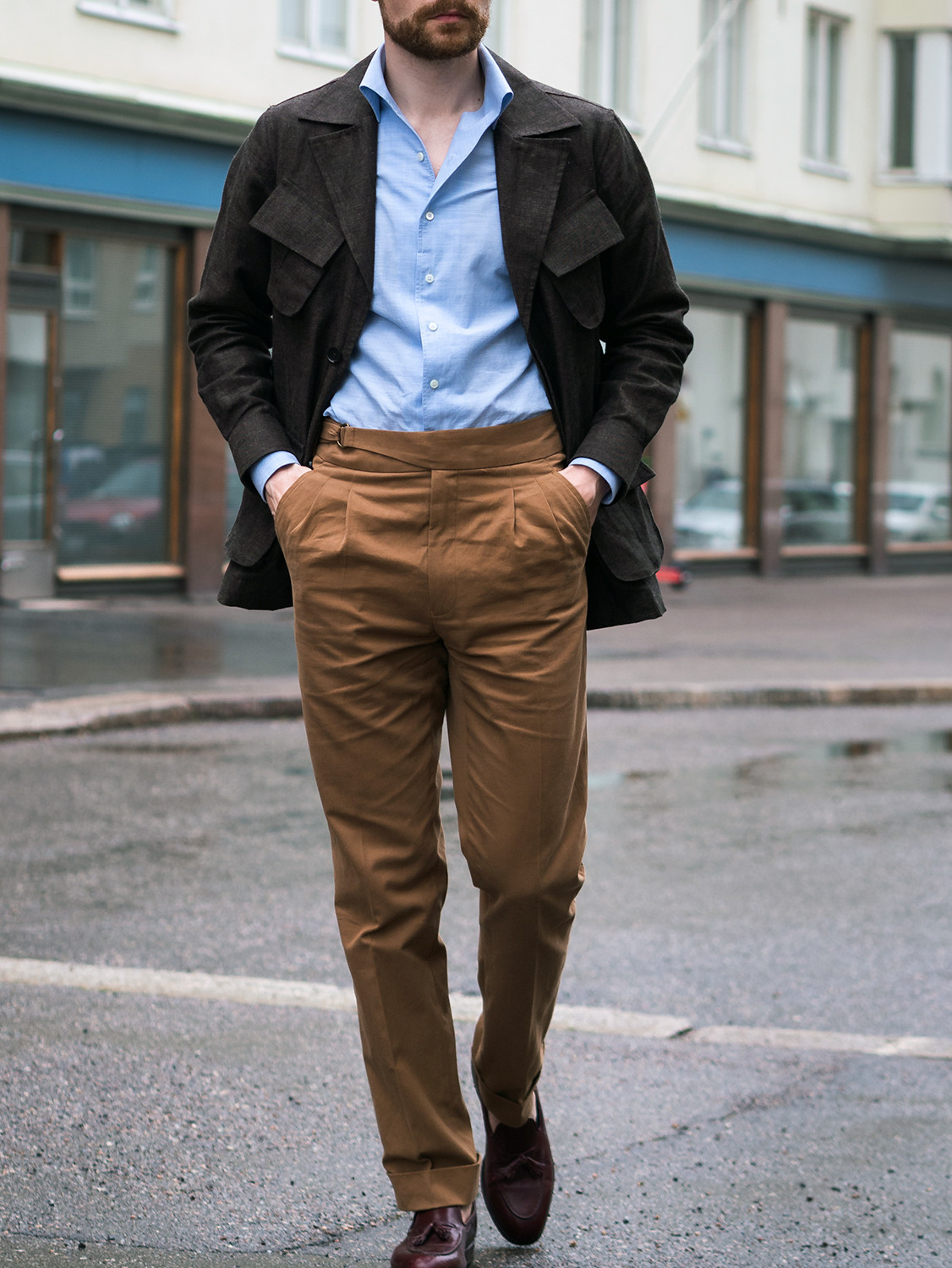 Men's outfit idea for 2021 with brown utility jacket, blue formal shirt, neutral plain formal trousers. Suitable for spring and autumn.