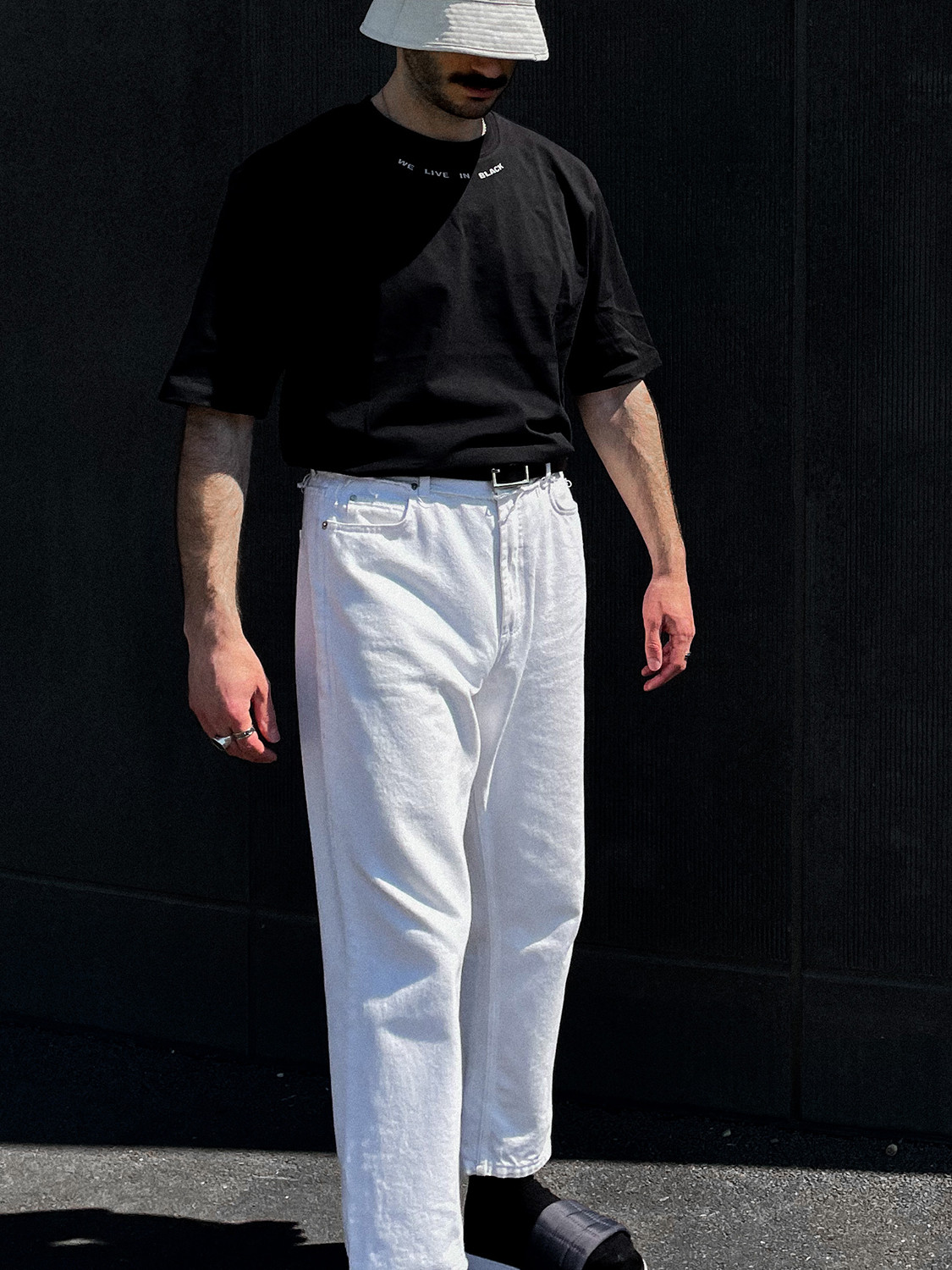 Men's outfit idea for 2021 with black crew neck t-shirt, white jeans, black flipflops. Suitable for summer.