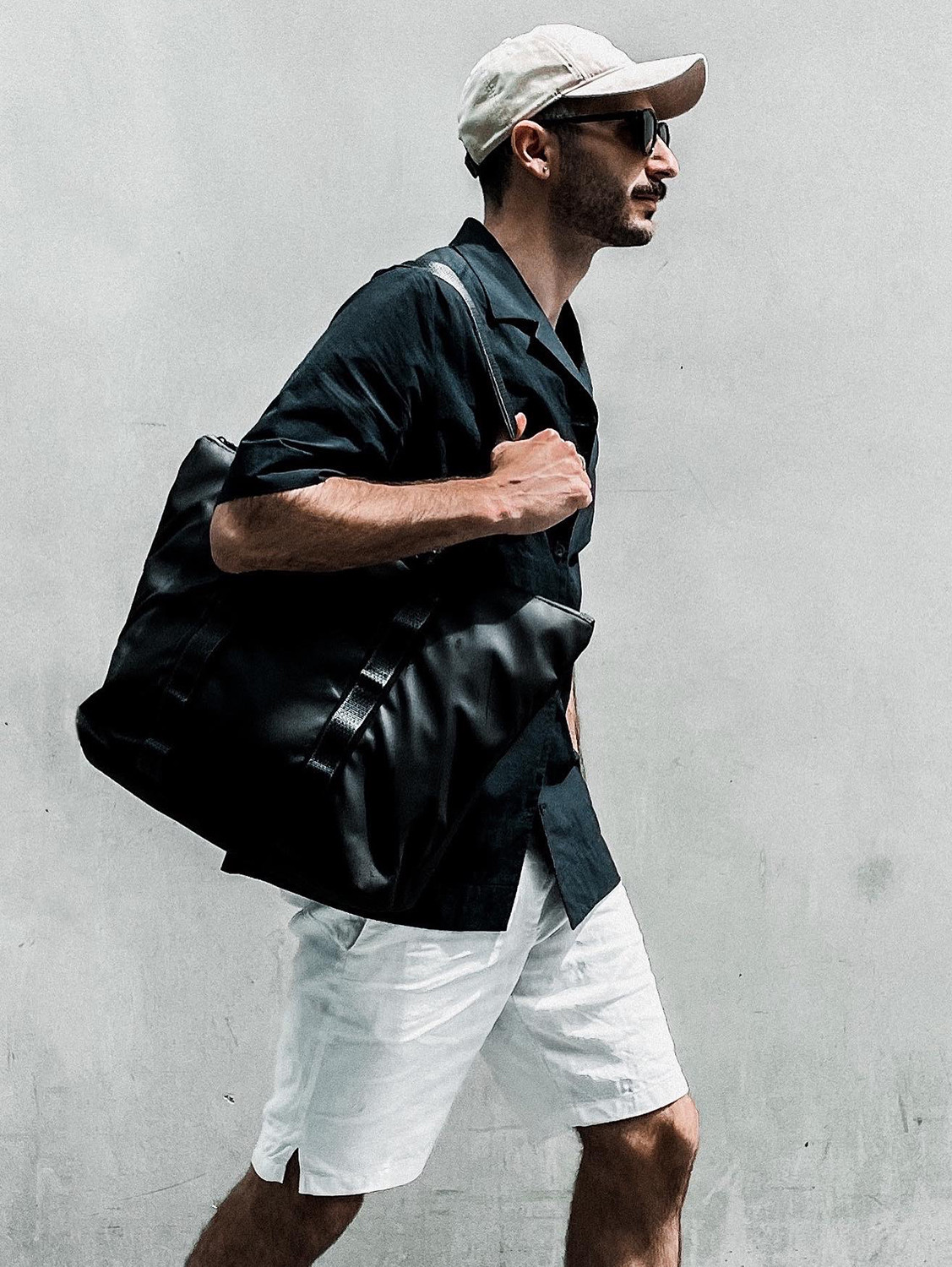 Men's outfit idea for 2021 with black short-sleeved plain shirt, white cotton shorts, black sandals. Suitable for summer.
