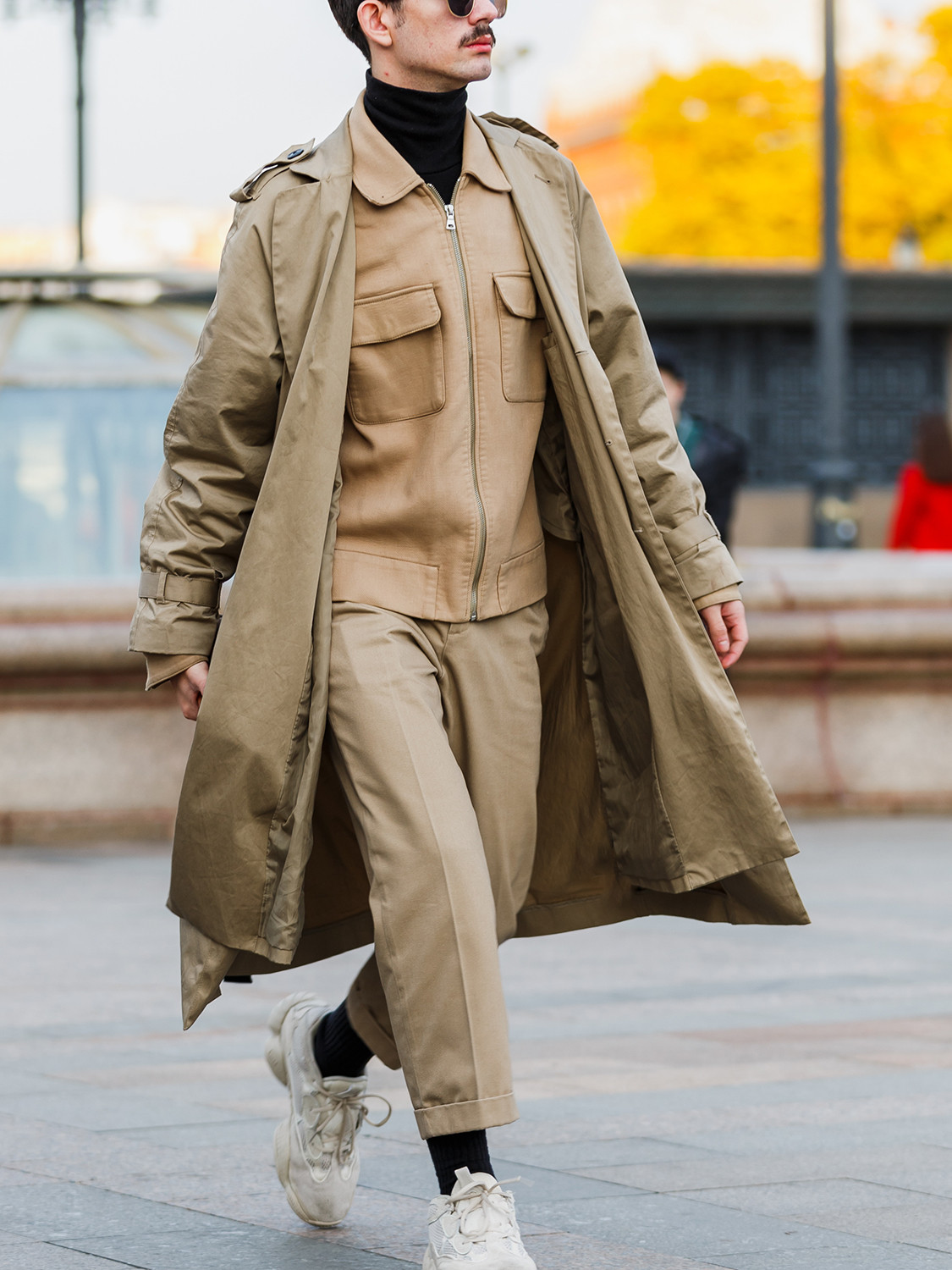 Men's outfit idea for 2021 with neutral trench coat, neutral utility jacket, black lightweight rollneck jumper, neutral chinos, neutral trainers / sneakers. Suitable for autumn.