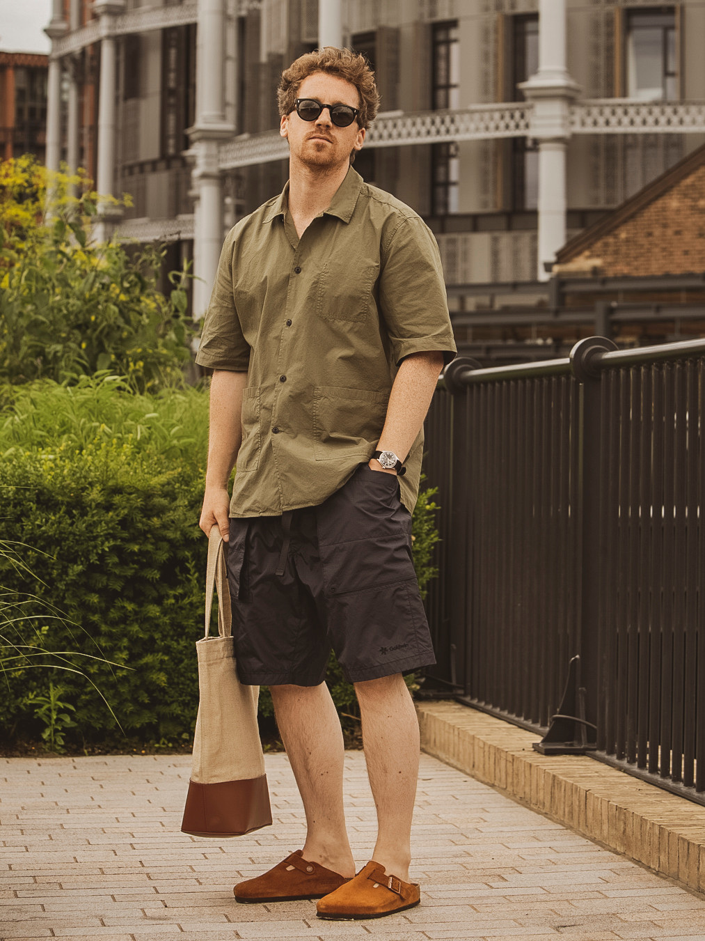 Men's outfit idea for 2021 with green short-sleeved plain shirt, brown cargo shorts. Suitable for spring and summer.
