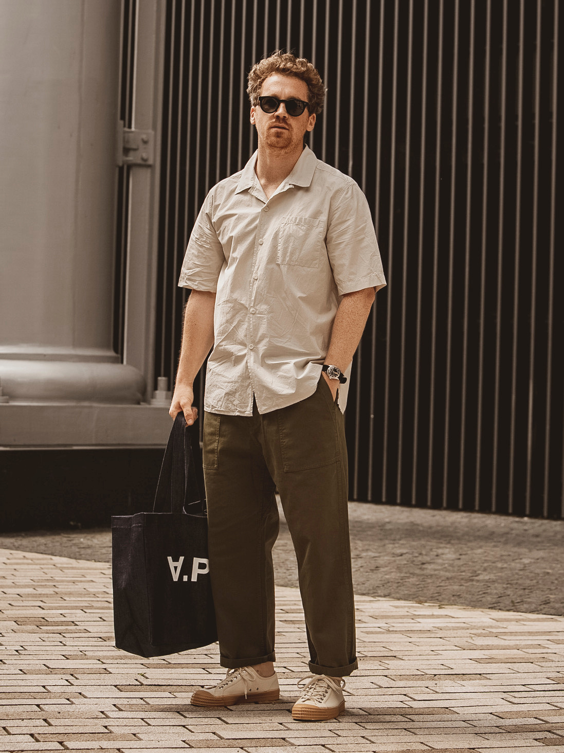 Men's outfit idea for 2021 with neutral short-sleeved plain shirt, green chinos, neutral sneakers. Suitable for spring and summer.