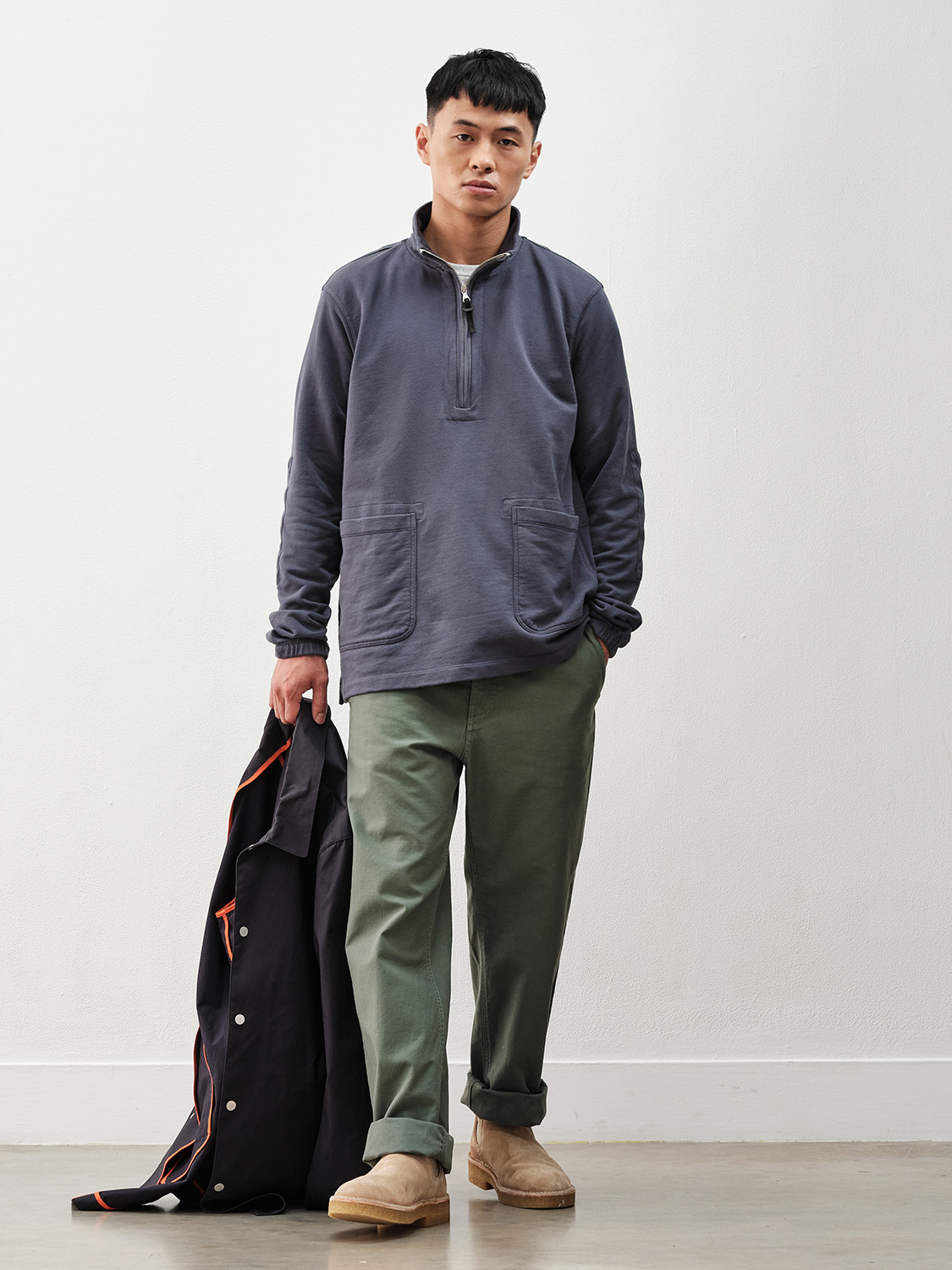 Men's outfit idea for 2021 with navy trench coat, white crew neck t-shirt, colored chinos, neutral chelsea boots. Suitable for spring and fall.