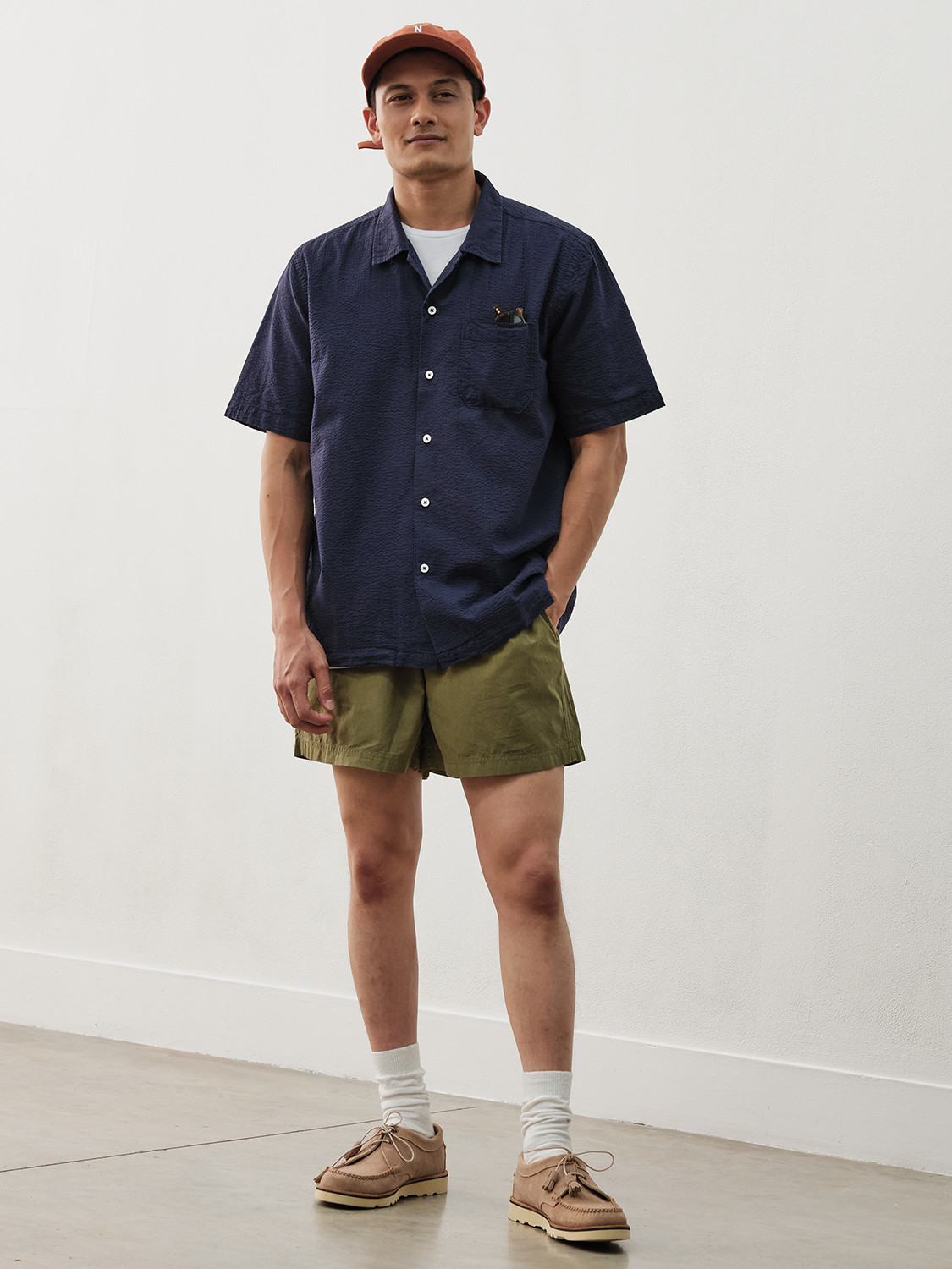 Men's outfit idea for 2021 with navy short-sleeved plain shirt, white crew neck t-shirt, green cotton shorts, neutral moccasins / wallabees. Suitable for spring and summer.