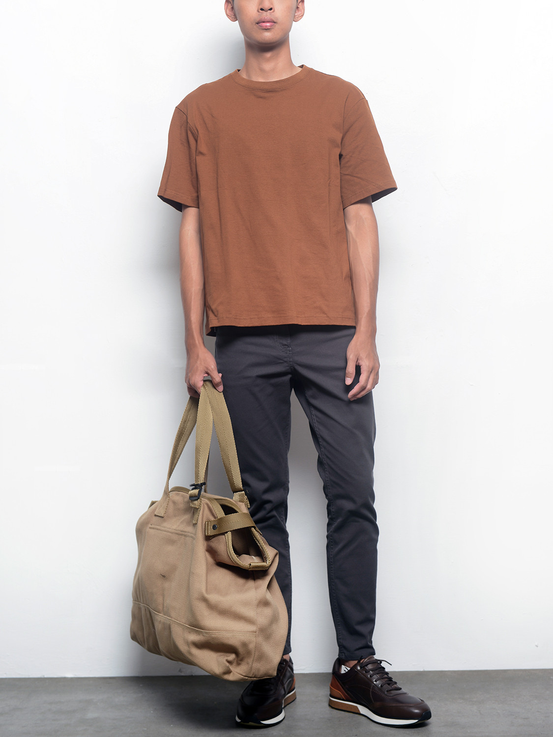Men's outfit idea for 2021 with neutral plain crew neck t-shirt, grey chinos, brown everyday trainers. Suitable for spring, summer and autumn.