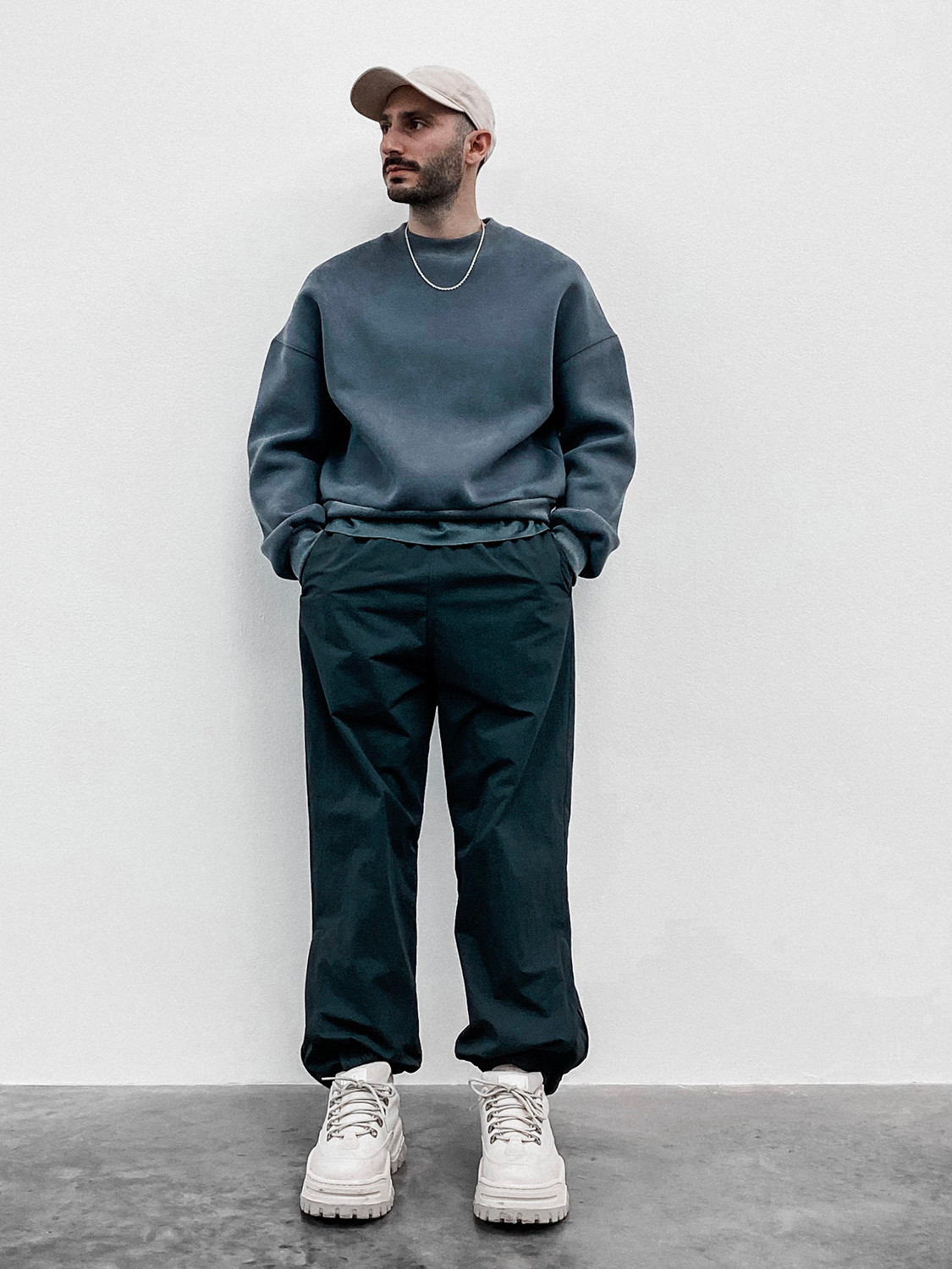 Men's outfit idea for 2021 with grey plain sweatshirt, black trackpants, neutral baseball / snapback cap, neutral sneakers. Suitable for fall and winter.