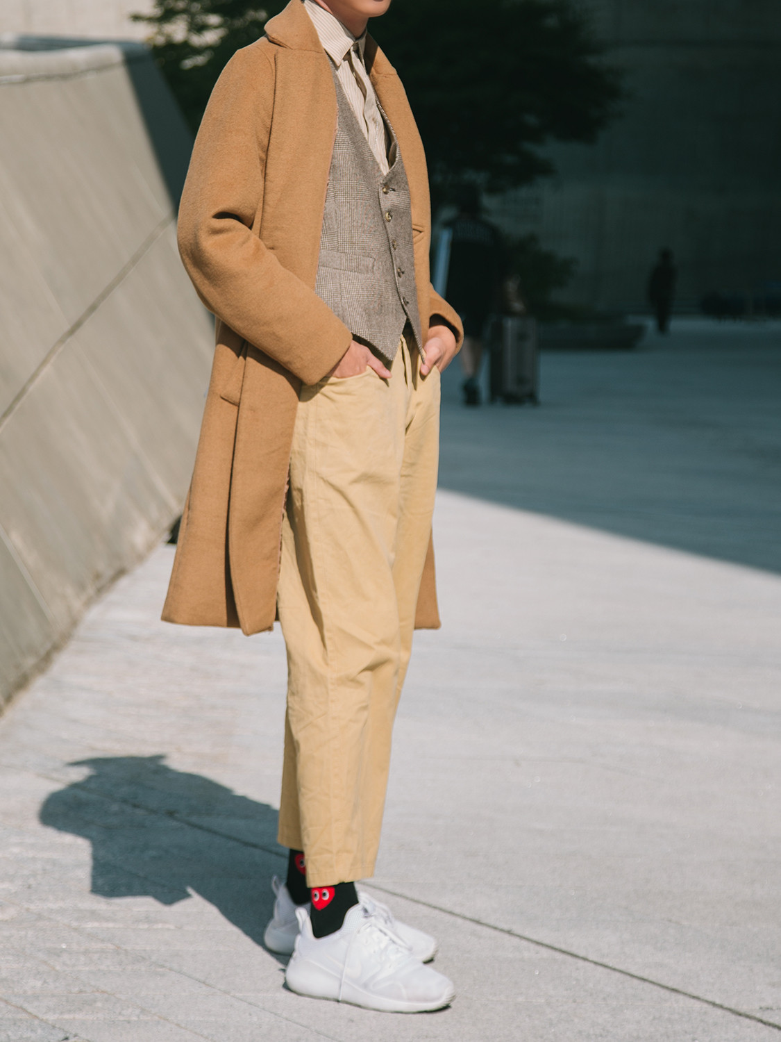Men's outfit idea for 2021 with neutral camel coat, neutral striped casual shirt, neutral chinos, white everyday trainers. Suitable for spring and autumn.