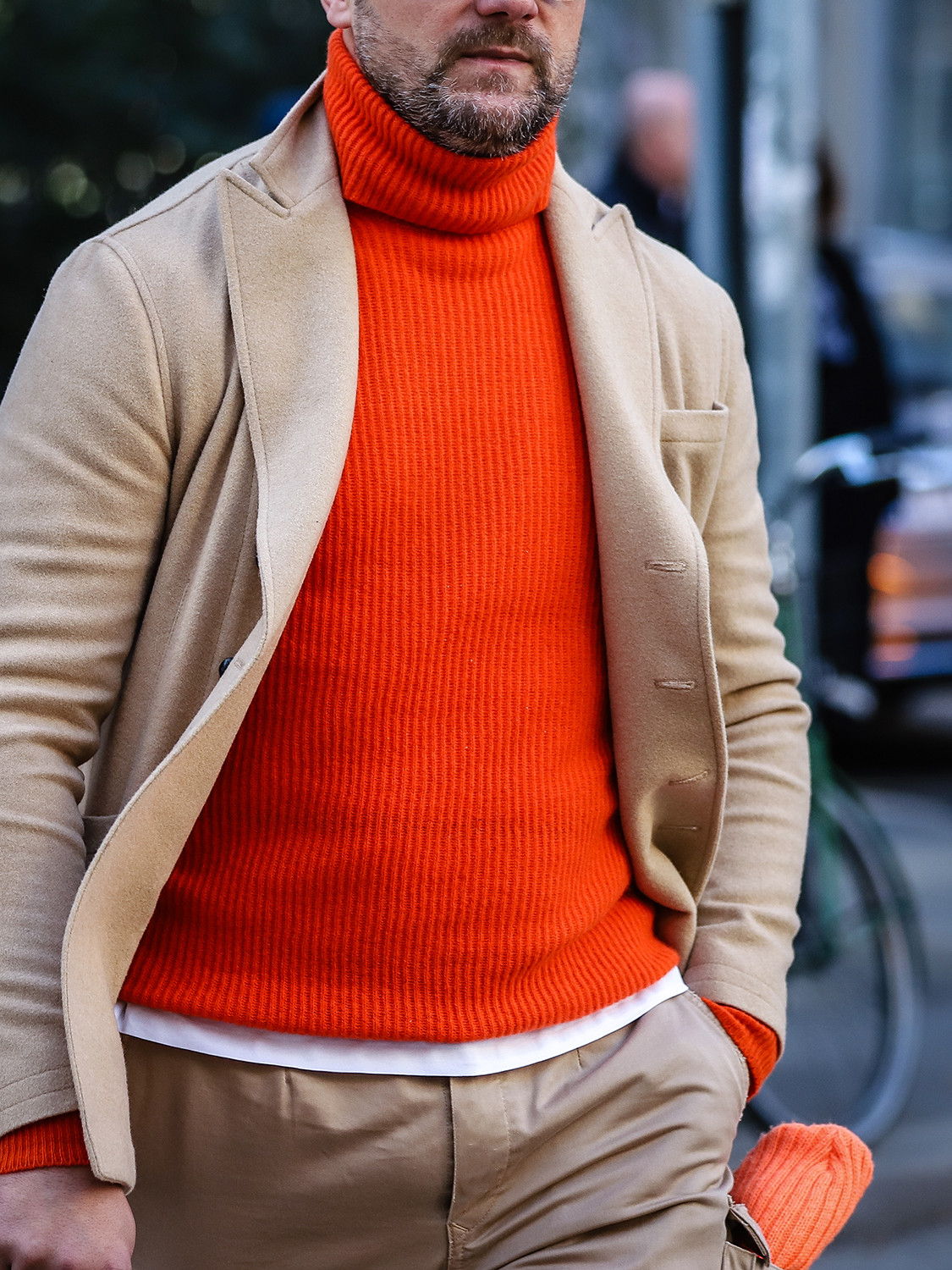 Men's outfit idea for 2021 with neutral single-breasted overcoat, orange plain crew neck knitted jumper, white crew neck t-shirt, stone chinos, lace-up leather boots. Suitable for autumn and winter.