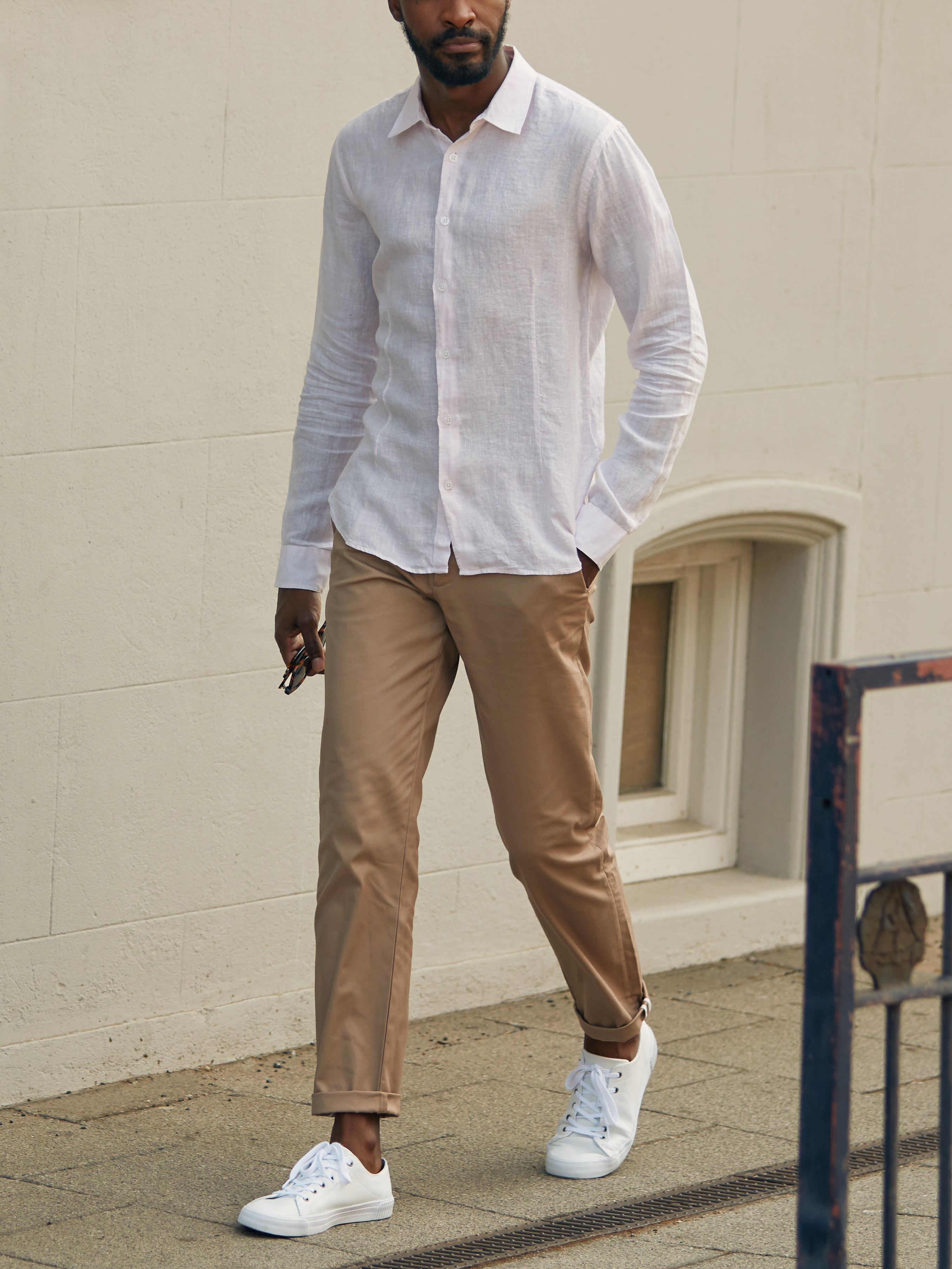 Men's outfit idea for 2021 with white linen shirt, stone chinos, white trainers. Suitable for spring and summer.
