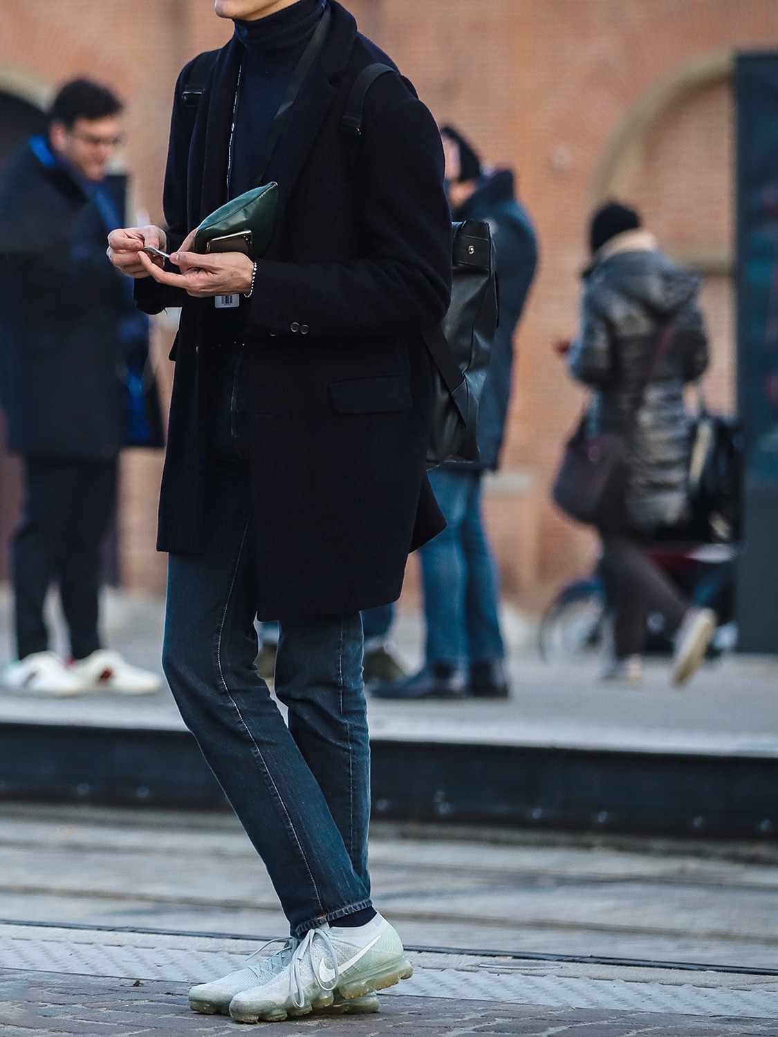 Men's outfit idea for 2021 with navy single-breasted overcoat, navy lightweight rollneck jumper, dark blue jeans, grey trainers / sneakers. Suitable for autumn and winter.