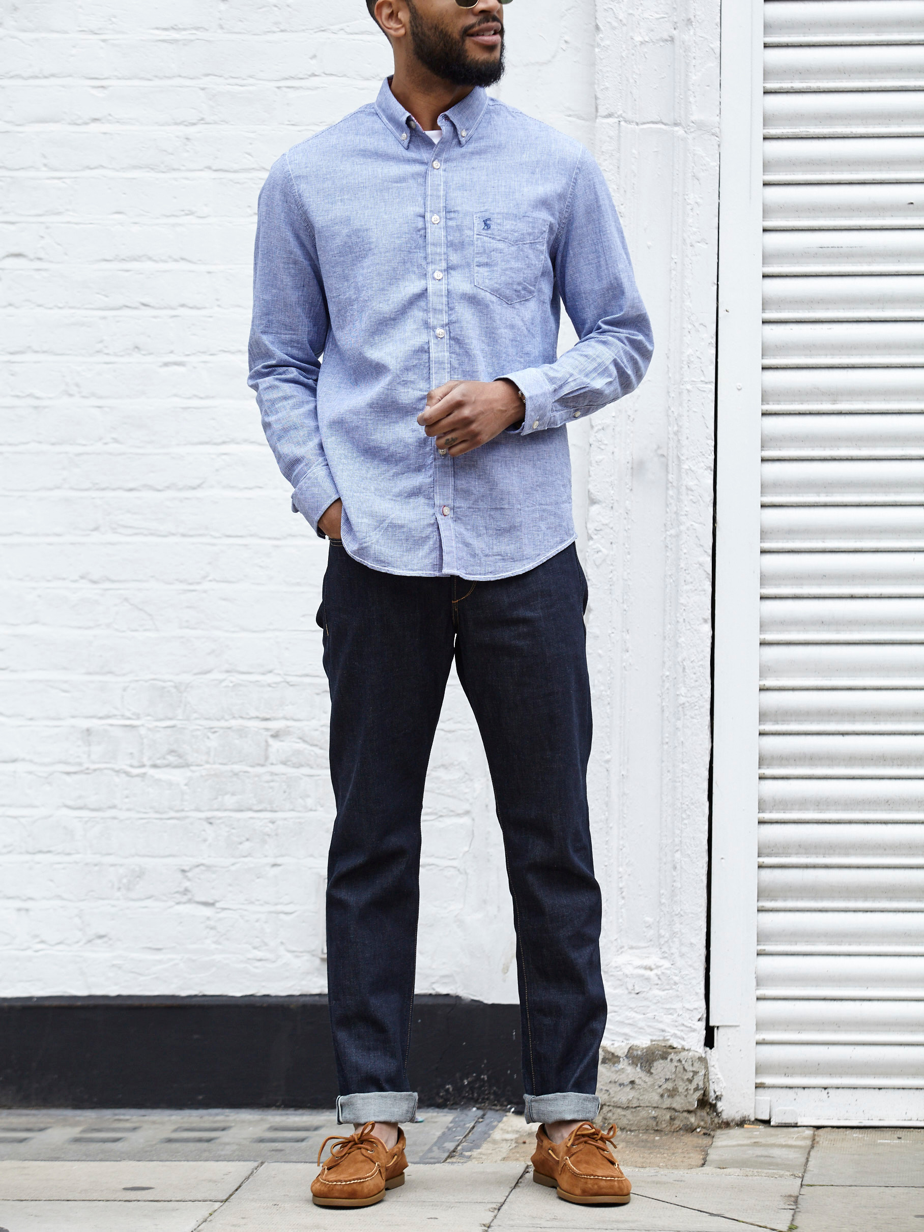 Men's outfit idea for 2021 with linen shirt, white crew neck t-shirt, dark blue jeans, boat shoes. Suitable for spring and summer.