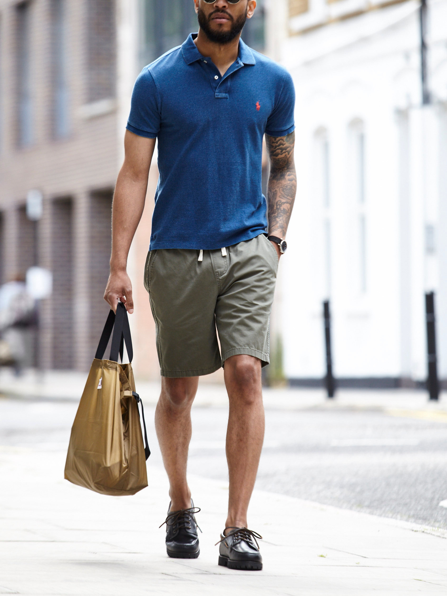 Men's outfit idea for 2021 with navy polo, khaki shorts, tote bag, boat shoes. Suitable for summer.