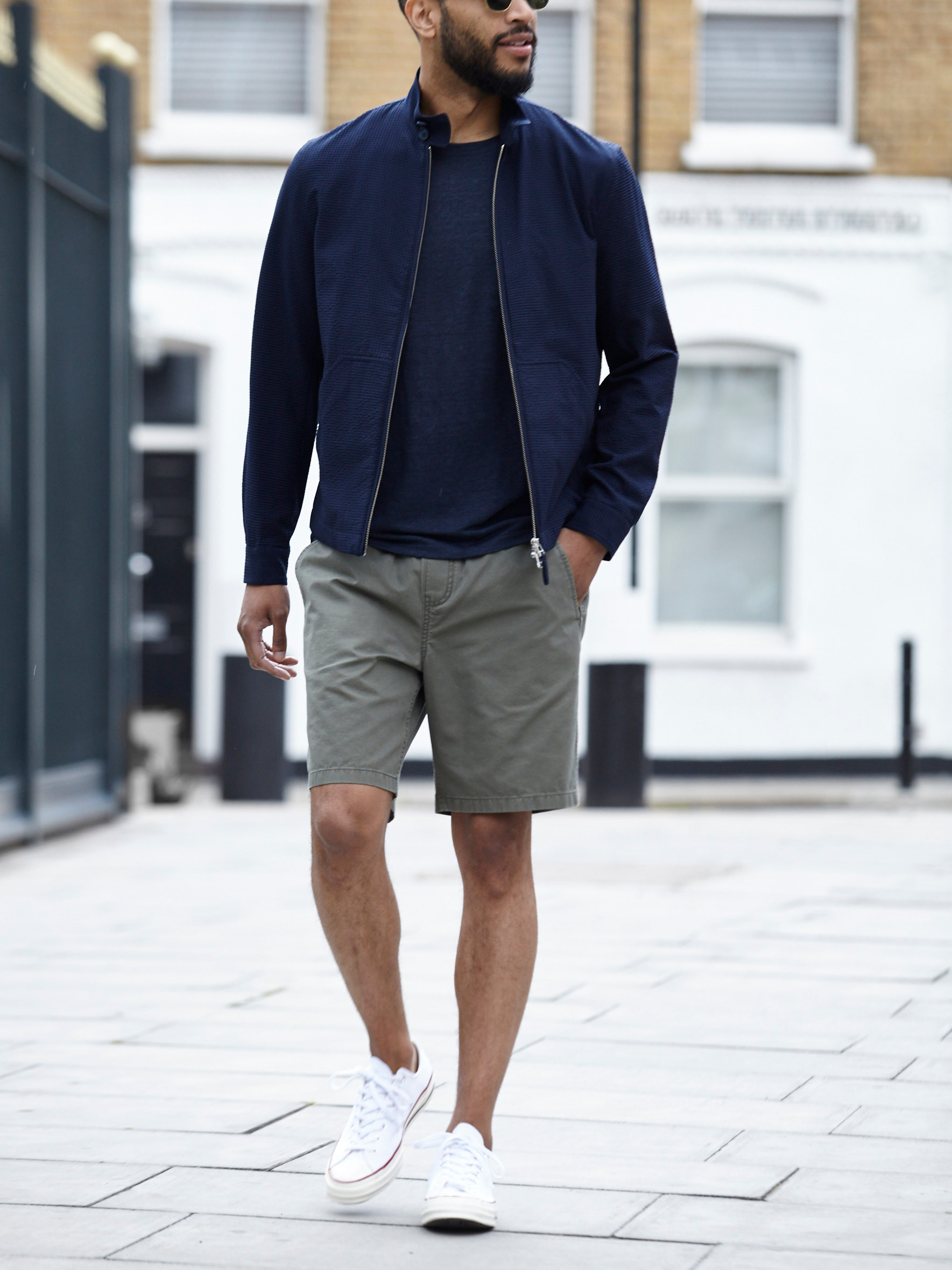 Men's outfit idea for 2021 with harrington jacket, navy crew neck t-shirt, khaki shorts, white trainers. Suitable for spring and summer.