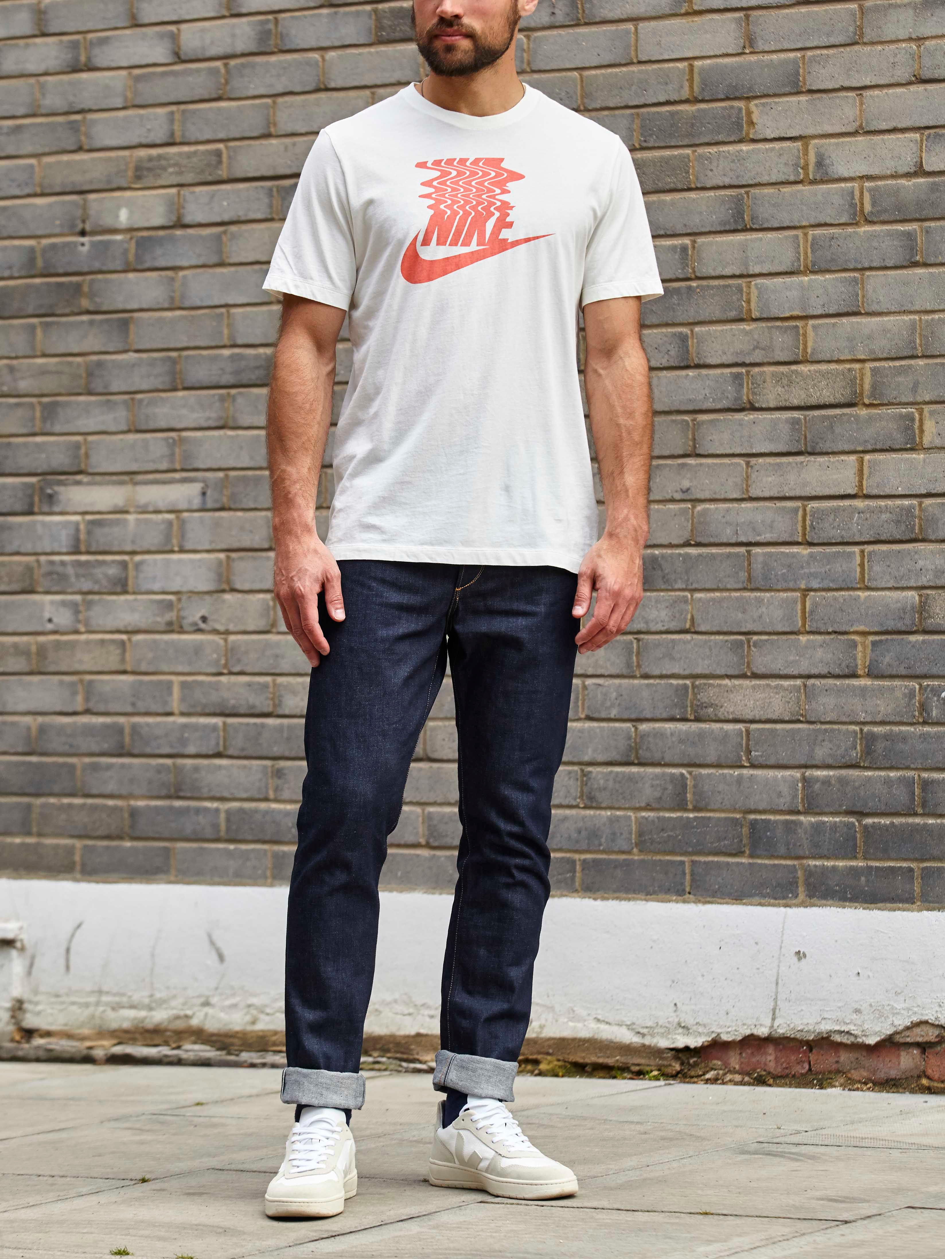 Men's outfit idea for 2021 with logo printed crew neck t-shirt, dark blue jeans, black sunglasses, neutral sneakers. Suitable for summer.