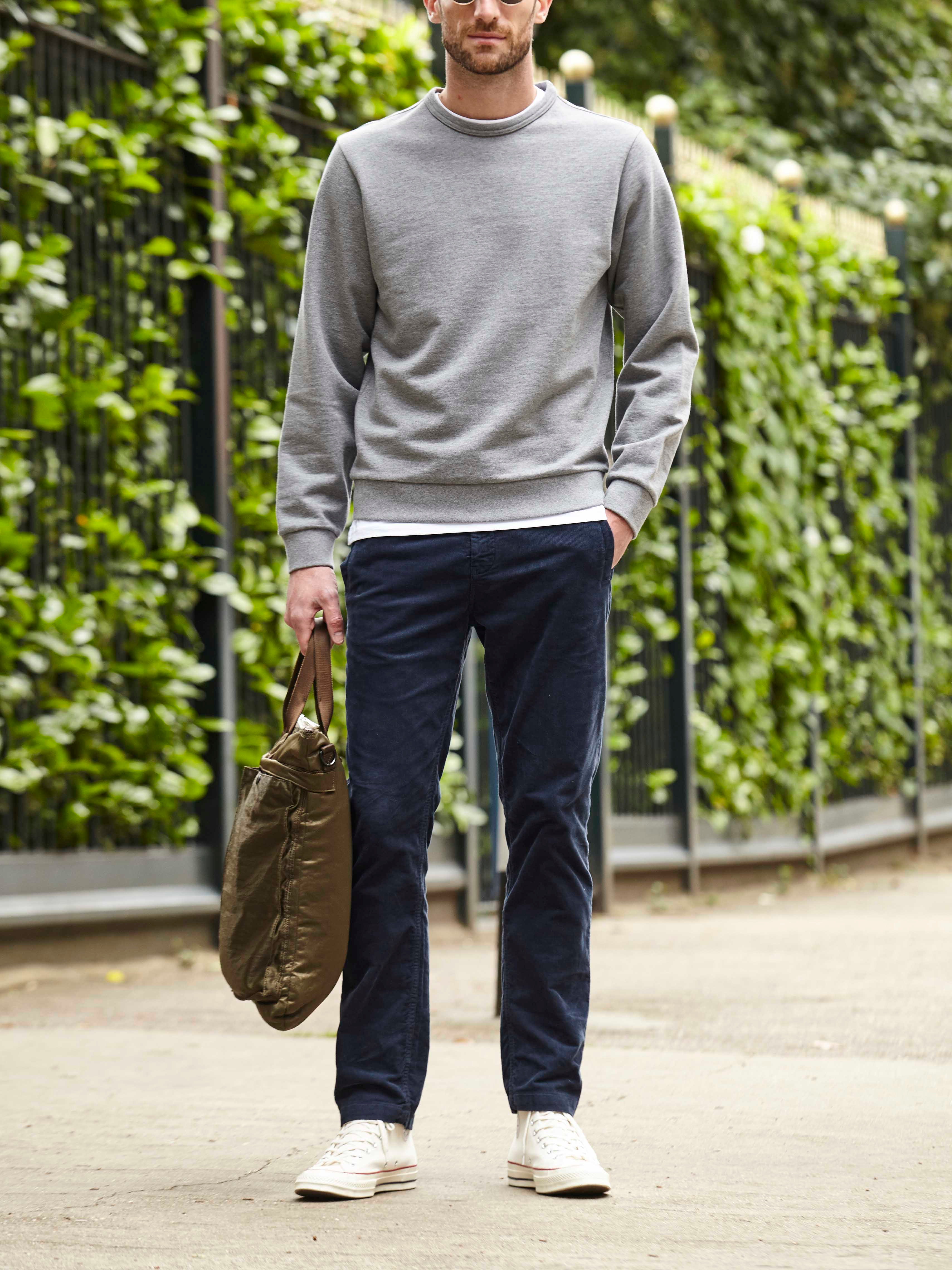 Men's outfit idea for 2021 with gray sweatshirt, white crew neck t-shirt, navy chinos, converse. Suitable for spring and fall.