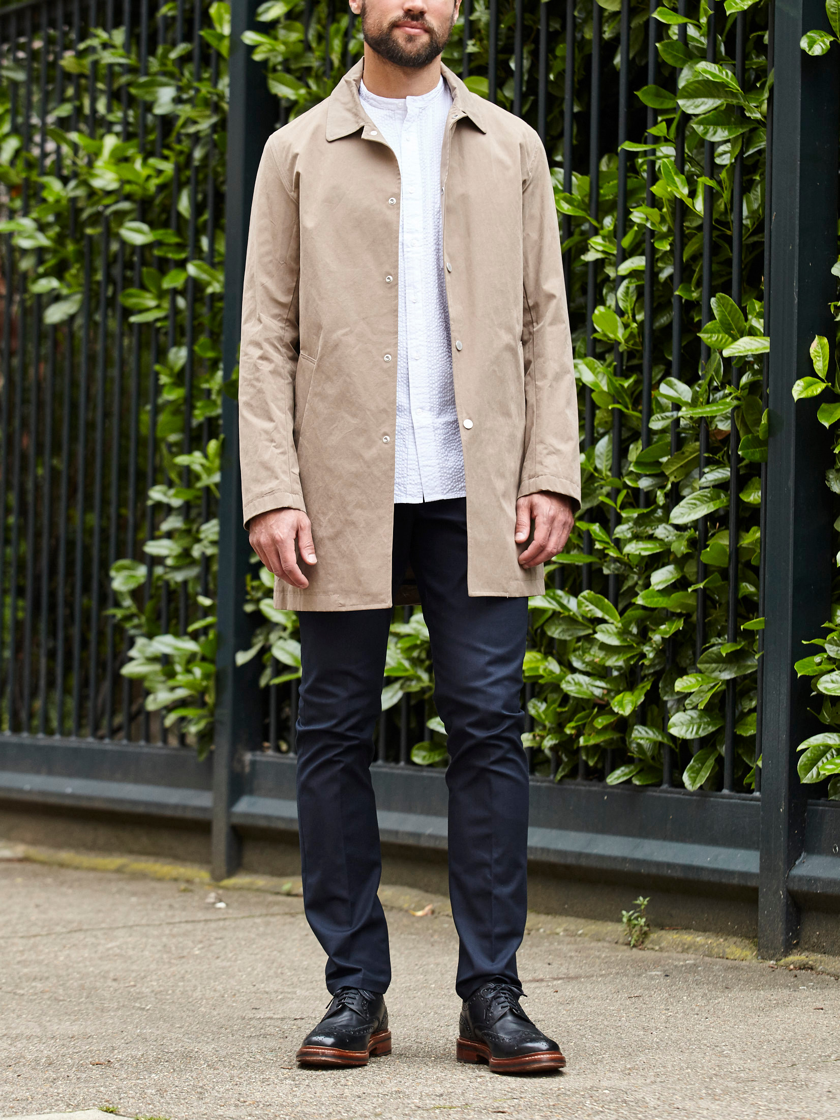 Men's outfit idea for 2021 with stone trench coat, white casual shirt, navy formal trousers, black brogues. Suitable for spring, summer and autumn.