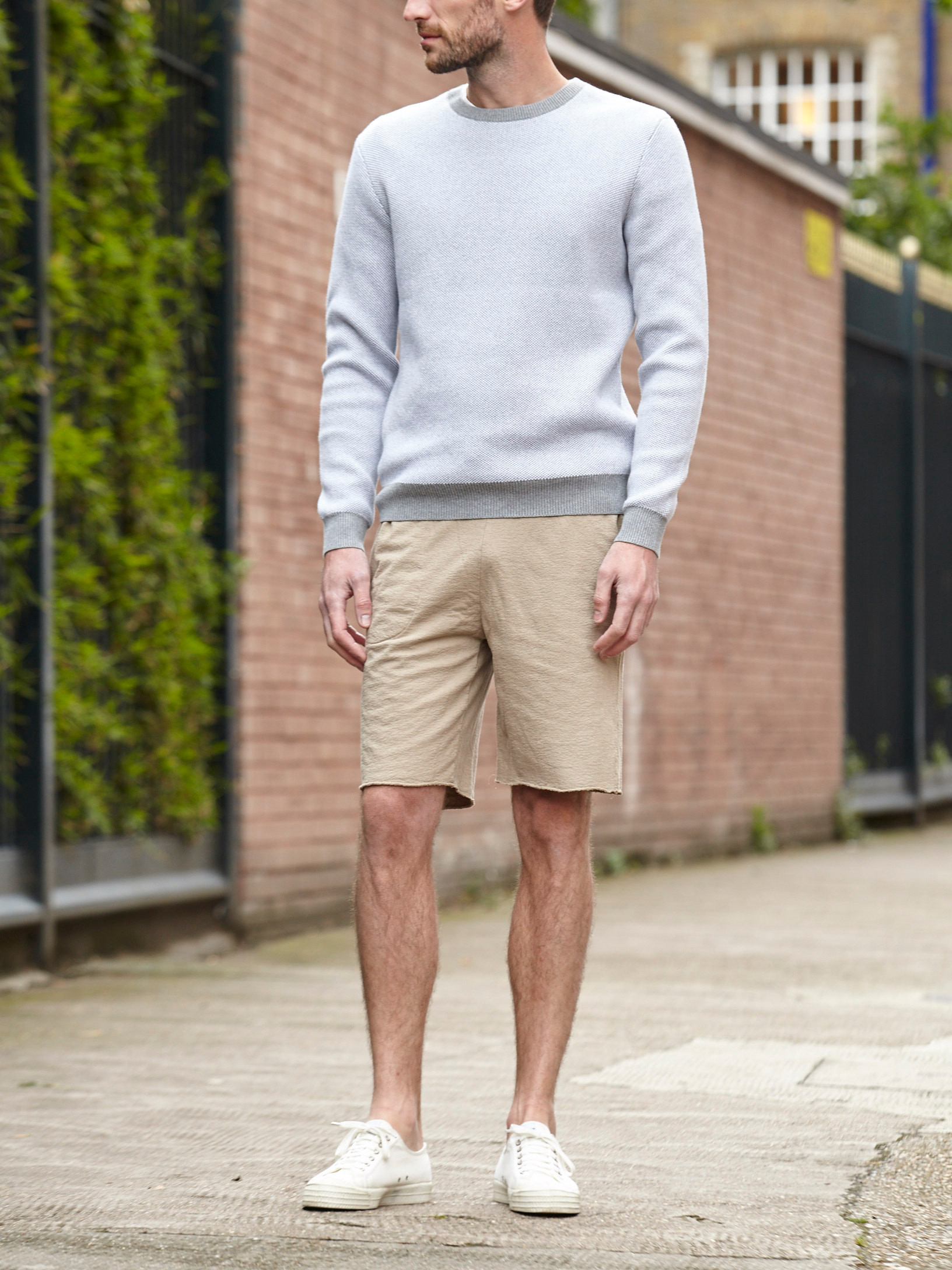 Men's outfit idea for 2021 with grey plain sweatshirt, sweat shorts, white trainers. Suitable for summer.