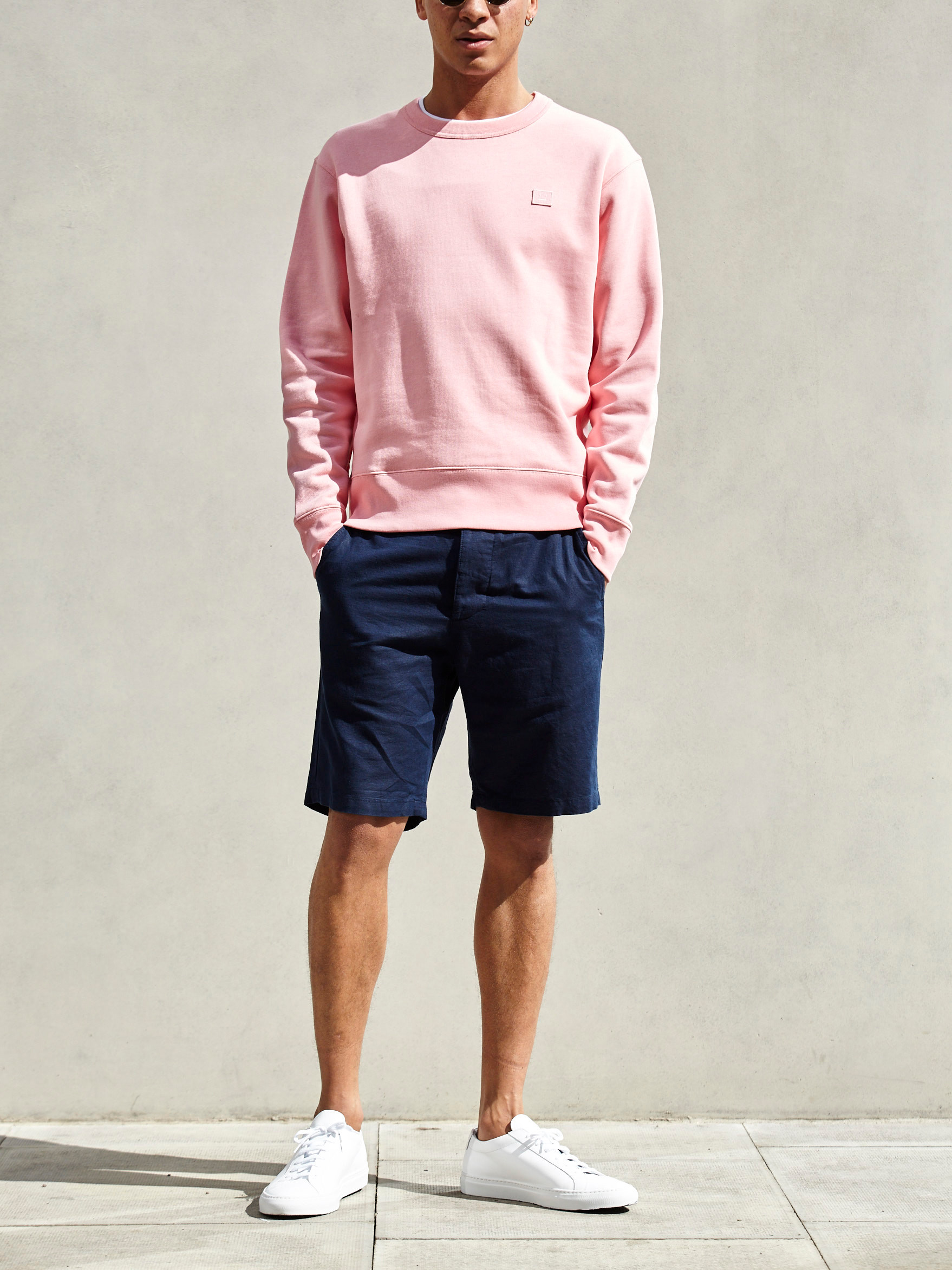 Men's outfit idea for 2021 with bold coloured sweatshirt, white crew neck t-shirt, navy shorts, tortoiseshell sunglasses, white trainers. Suitable for summer.