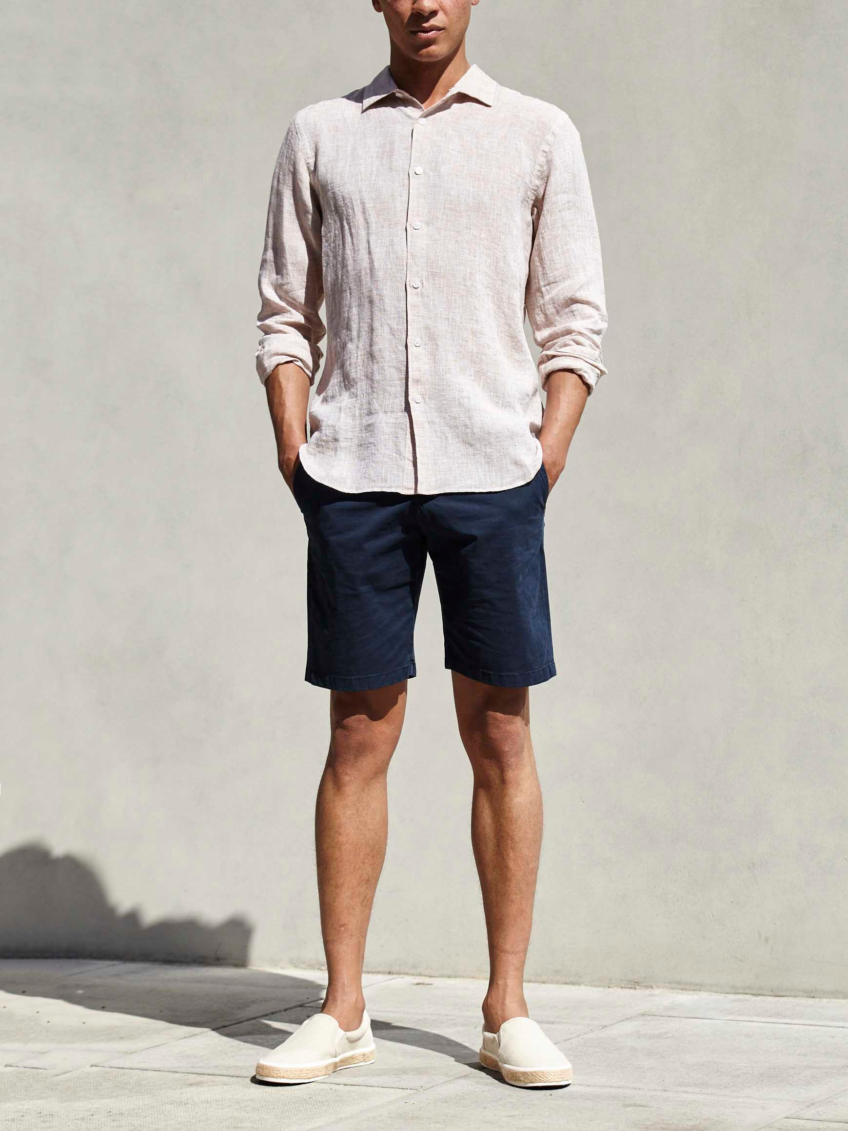 Men's outfit idea for 2021 with linen shirt, navy shorts, tortoiseshell sunglasses, espadrilles. Suitable for summer.