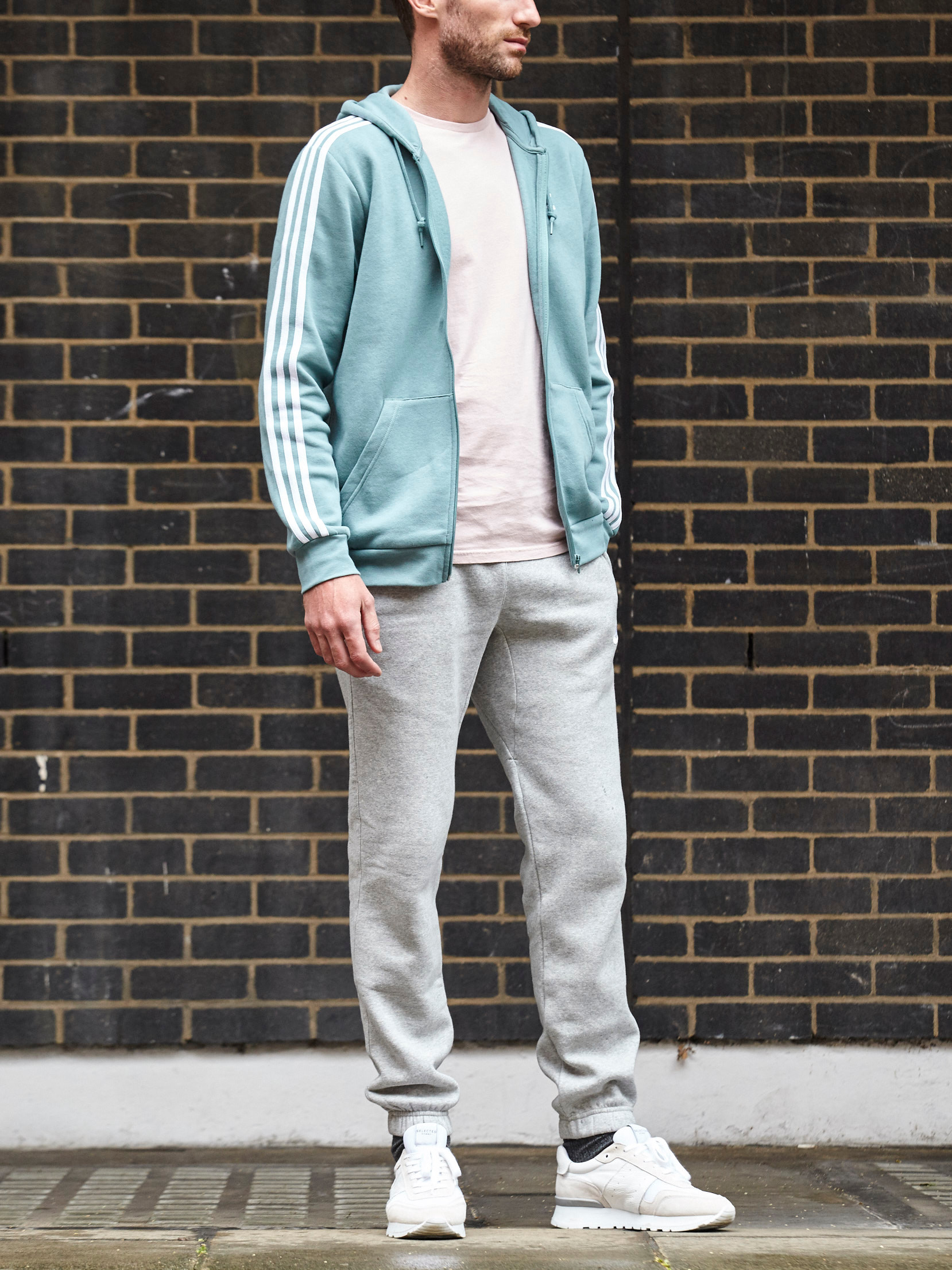 Men's outfit idea for 2021 with blue hoody, pale-colored crew neck t-shirt, sweatpants, white sneakers. Suitable for spring and fall.