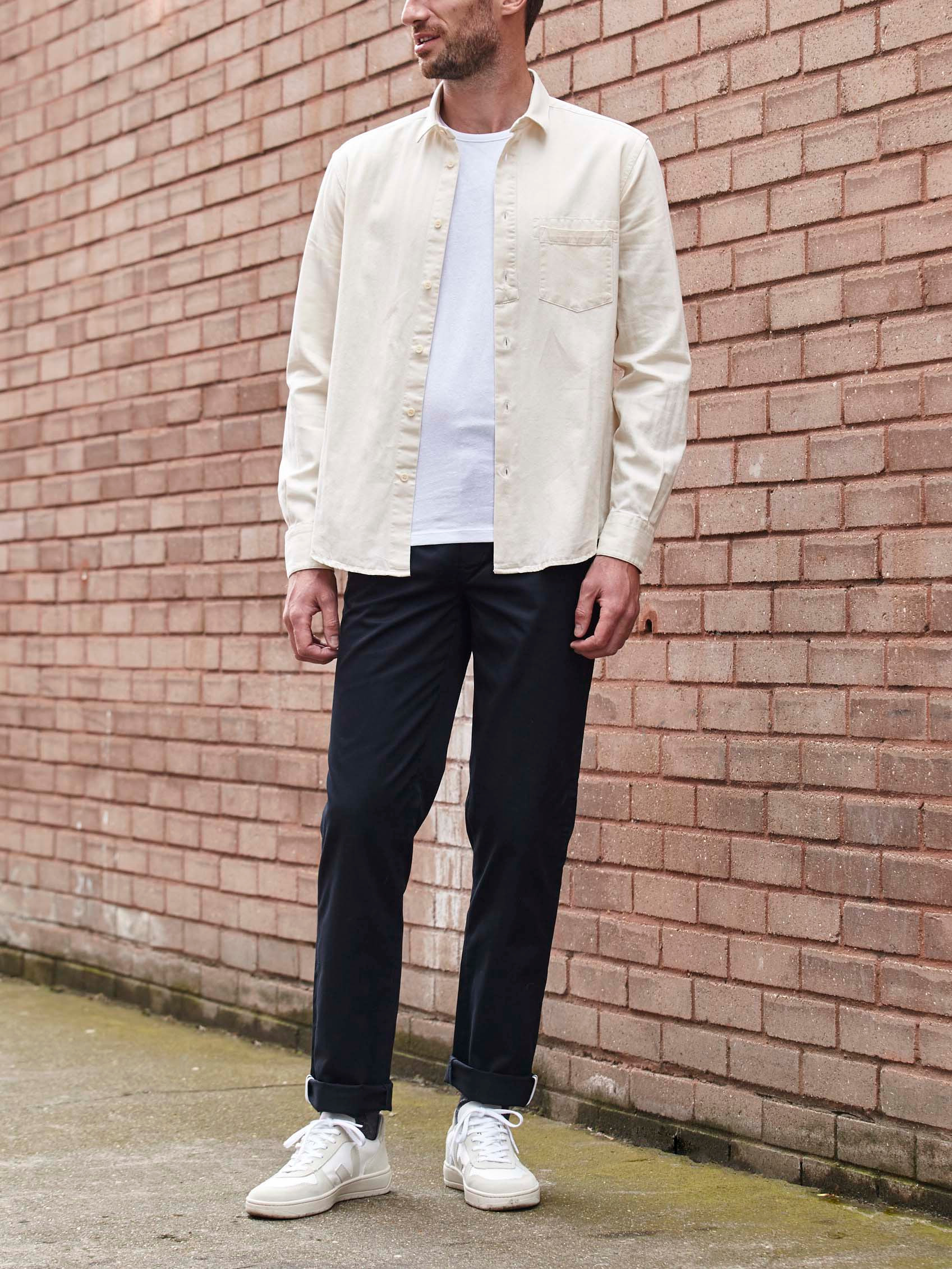 Men's outfit idea for 2021 with pale coloured casual shirt, white crew neck t-shirt, navy chinos, white trainers. Suitable for spring, summer and autumn.