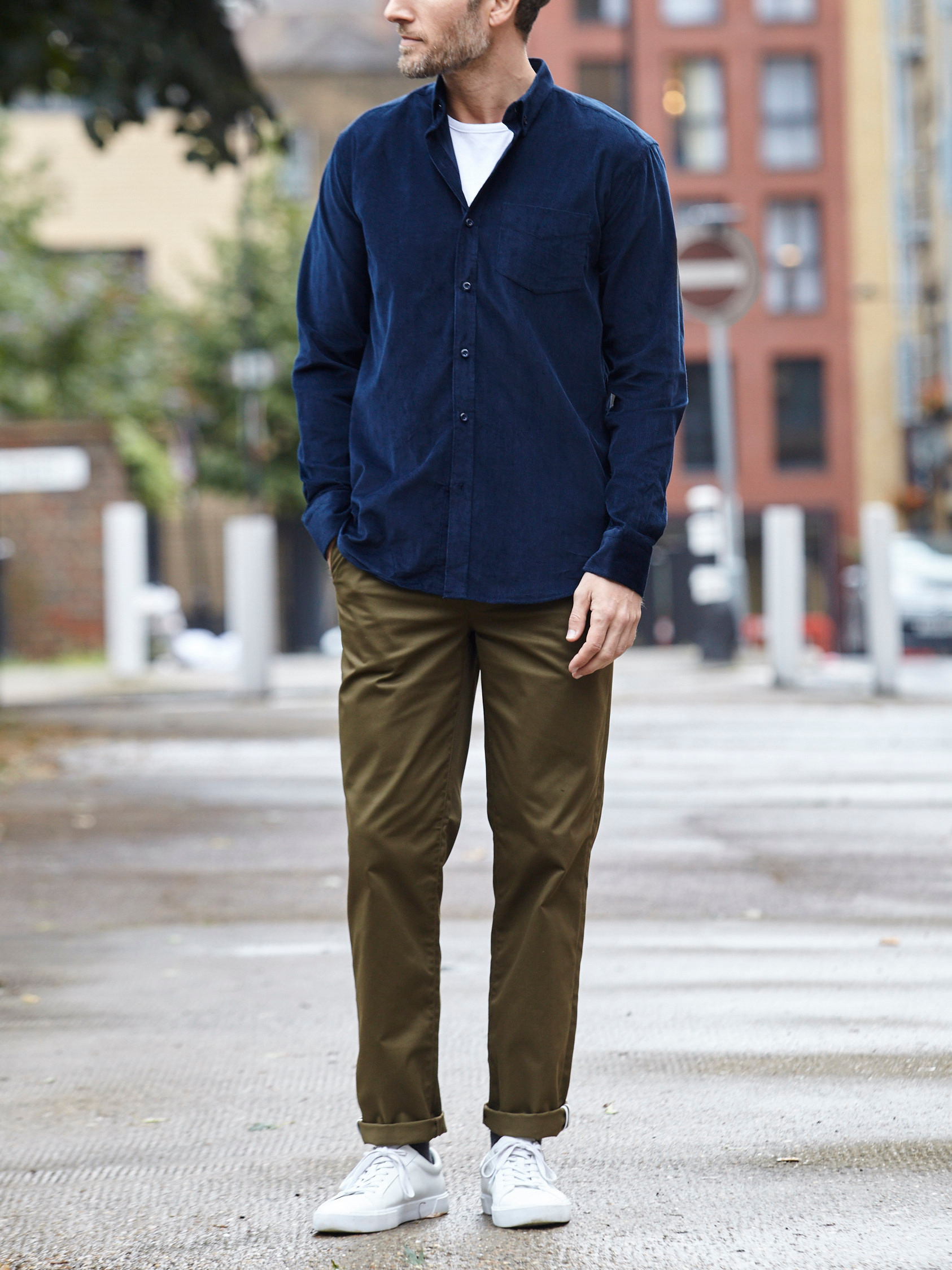 Men's outfit idea for 2021 with navy casual shirt, white crew neck t-shirt, colored chinos, white sneakers. Suitable for fall and winter.