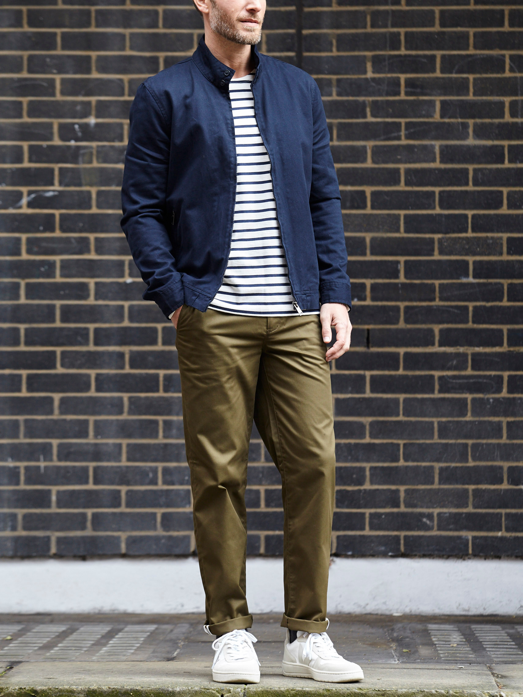 Men's outfit idea for 2021 with bomber jacket, striped crew neck t-shirt, colored chinos, white sneakers. Suitable for spring, fall and winter.