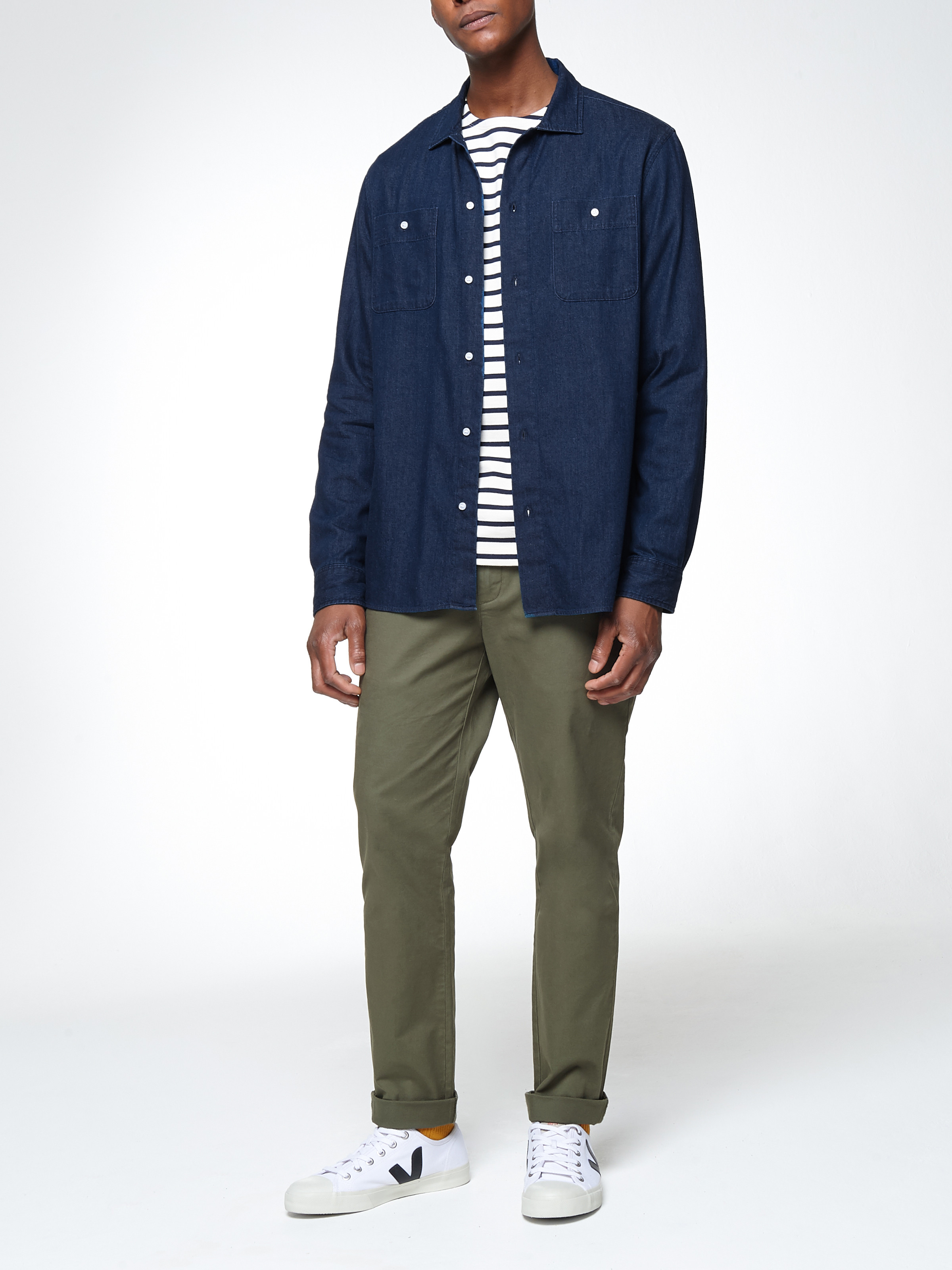 Men's outfit idea for 2021 with blue denim shirt, striped long-sleeved t-shirt, colored chinos, white sneakers. Suitable for spring and fall.