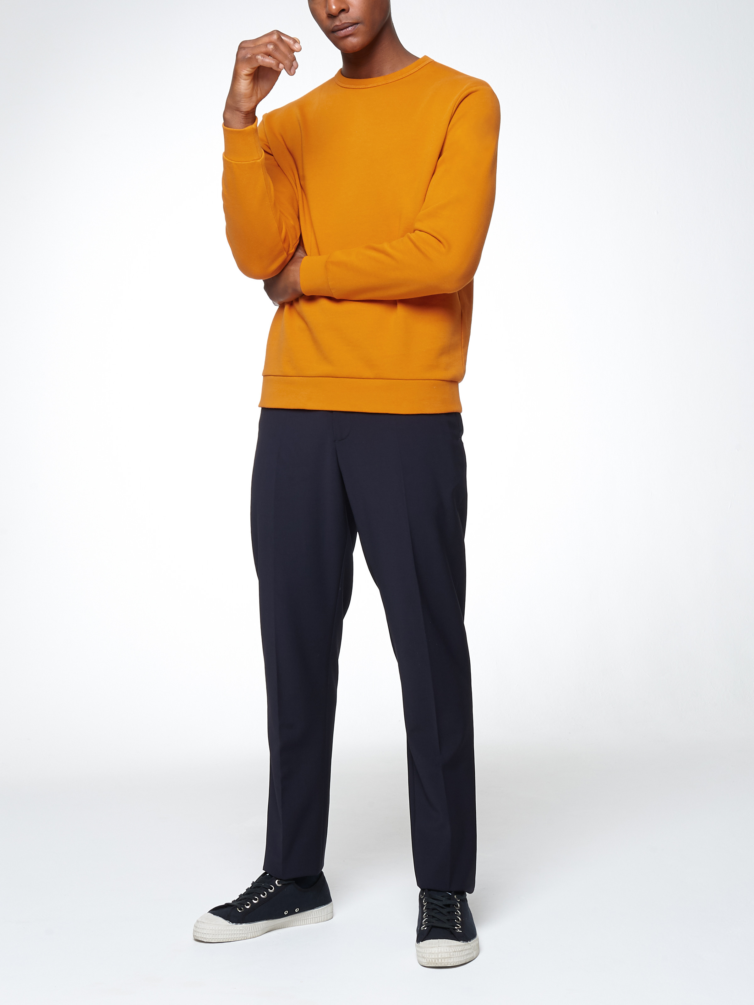 Men's outfit idea for 2021 with bold coloured sweatshirt, grey crew neck t-shirt, navy formal trousers, black trainers. Suitable for spring and autumn.
