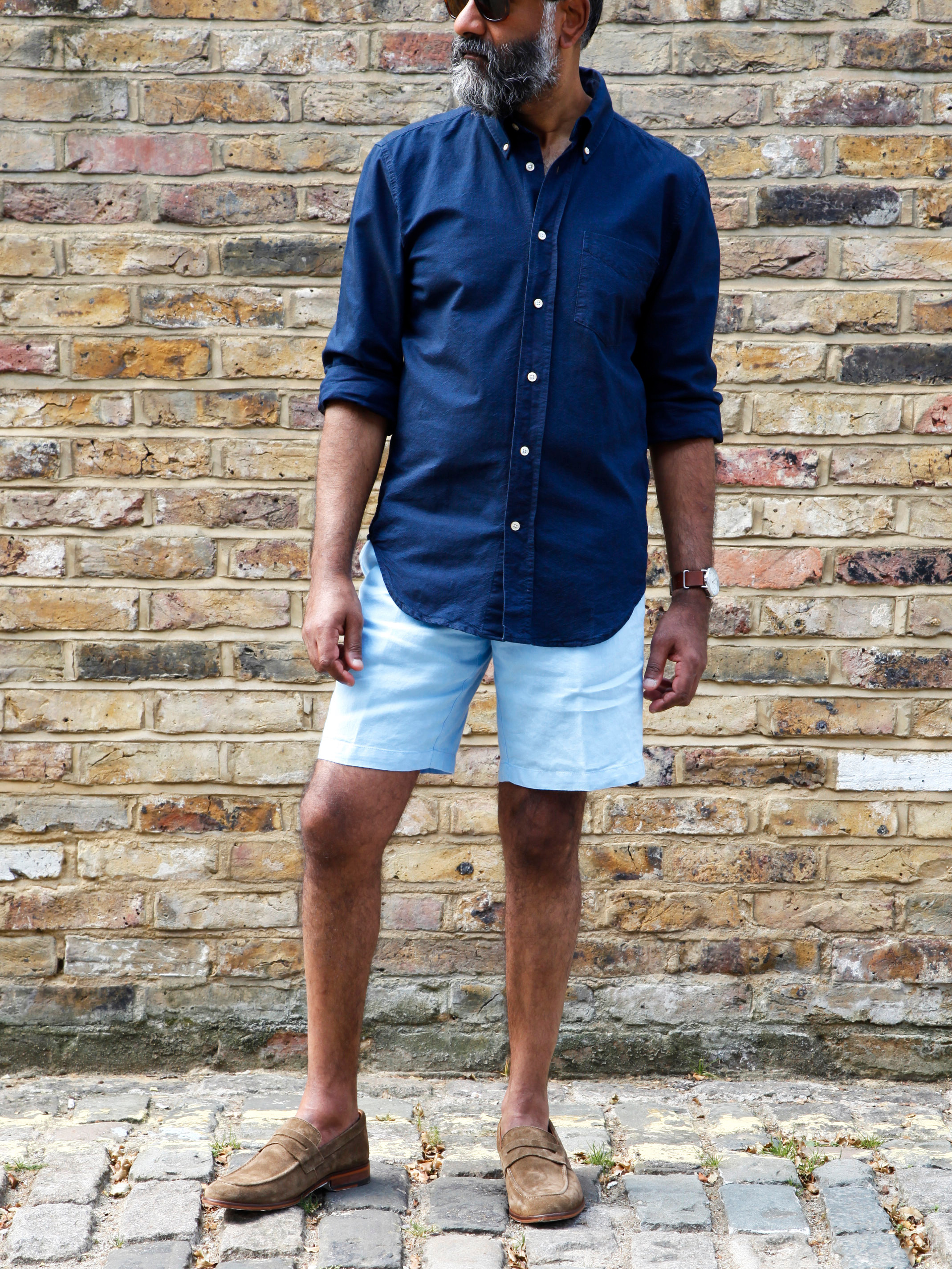 Men's outfit idea for 2021 with navy casual shirt, tailored shorts, tortoiseshell sunglasses, loafers. Suitable for summer.