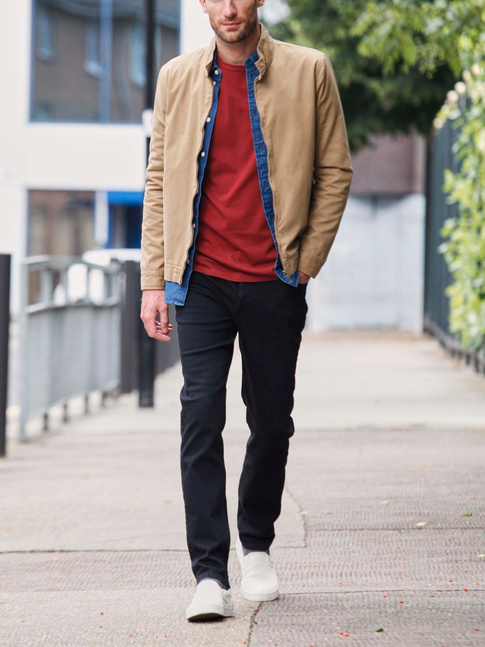 Men's outfit idea for 2021 with harrington jacket, denim shirt, bold-colored crew neck t-shirt, black jeans, plimsolls. Suitable for spring and fall.