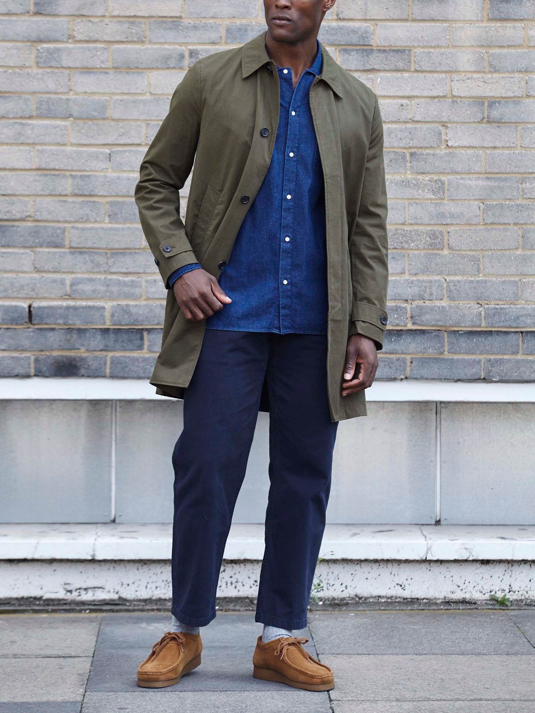 Men's outfit idea for 2021 with stone trench coat, denim shirt, navy chinos, neutral moccasins / wallabees. Suitable for spring and fall.