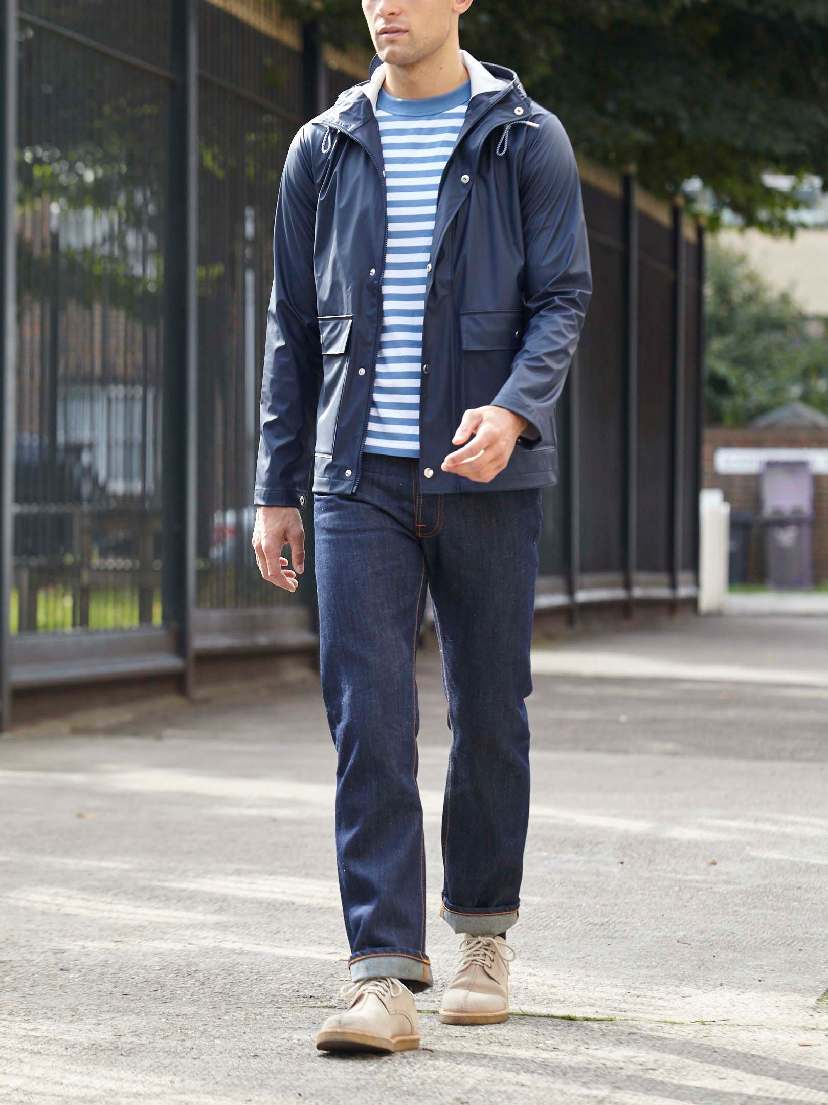 Men's outfit idea for 2021 with navy raincoat, blue striped crew neck t-shirt, dark blue jeans, moccasins / wallabees. Suitable for spring and fall.