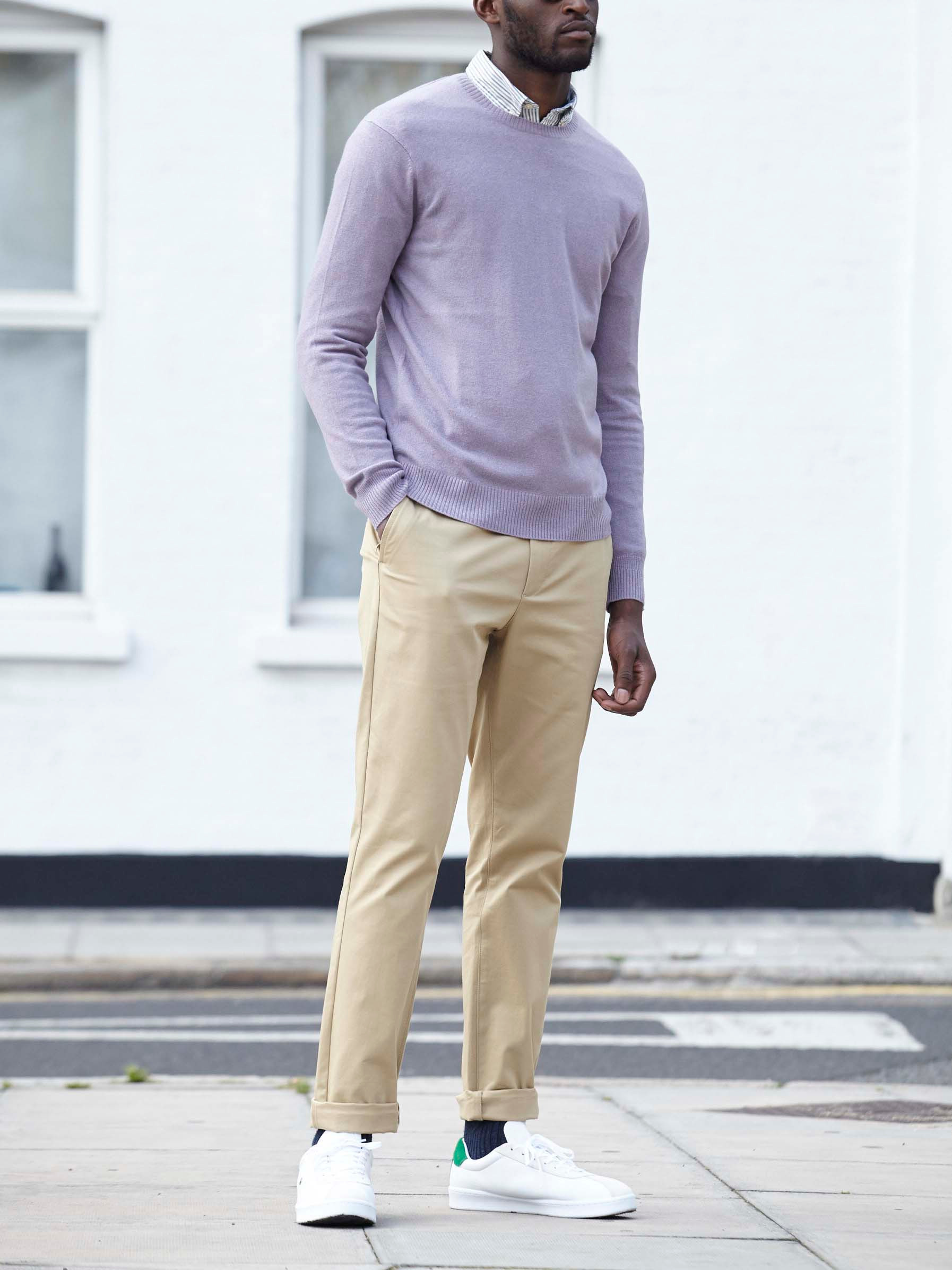Men's outfit idea for 2021 with pale coloured crew neck jumper, striped casual shirt, stone chinos, white trainers. Suitable for spring and autumn.