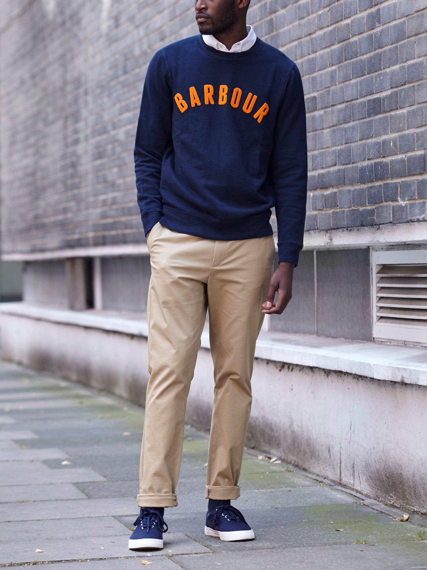 Men's outfit idea for 2021 with logo / printed sweatshirt, stone chinos, neutral sneakers. Suitable for spring and fall.