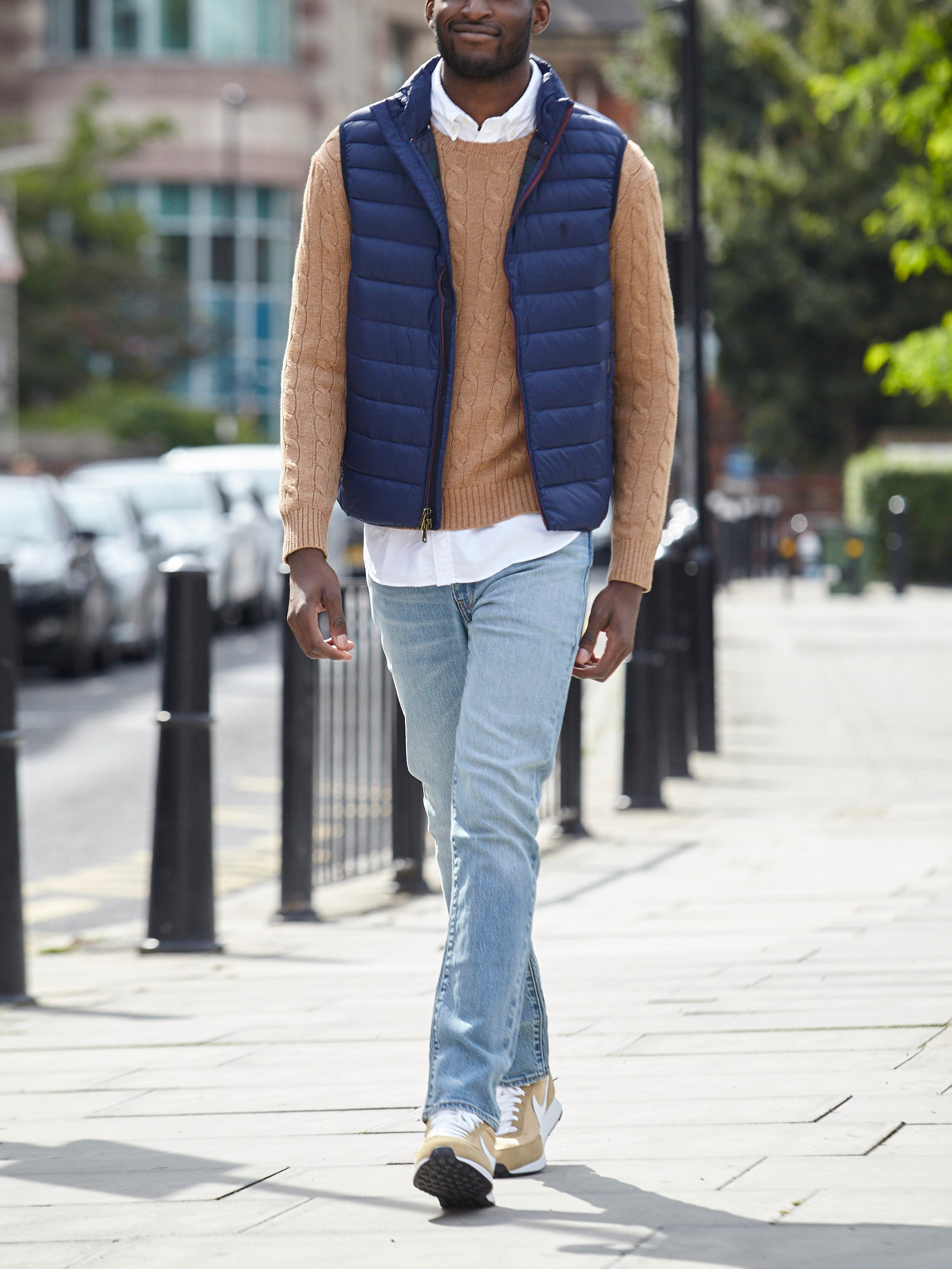 Men's outfit idea for 2021 with vest, cable-knit sweater, white casual shirt, light blue jeans, neutral sneakers. Suitable for spring and fall.