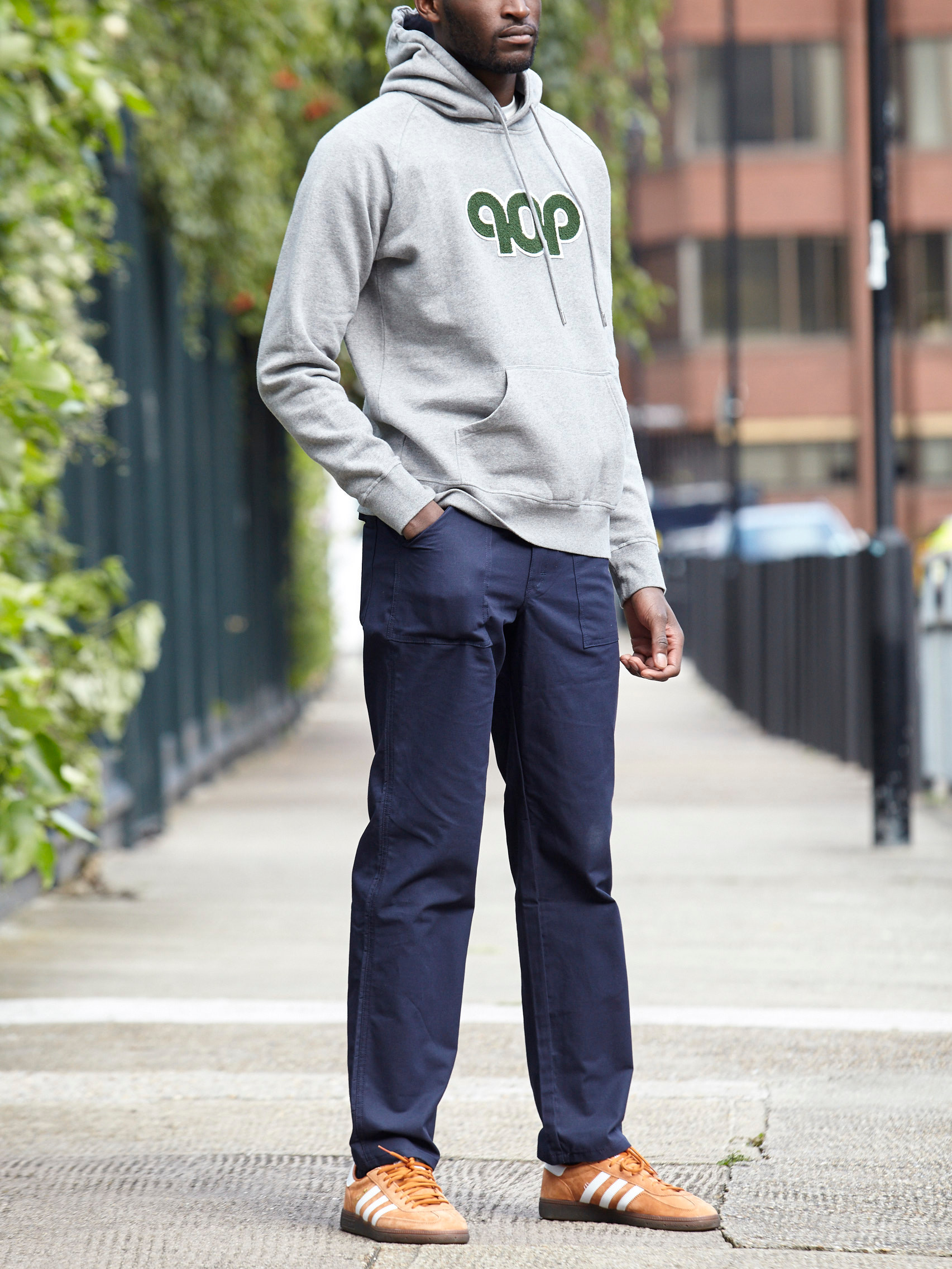 Men's outfit idea for 2021 with logo / printed hoodie, navy chinos, bright sneakers. Suitable for fall.