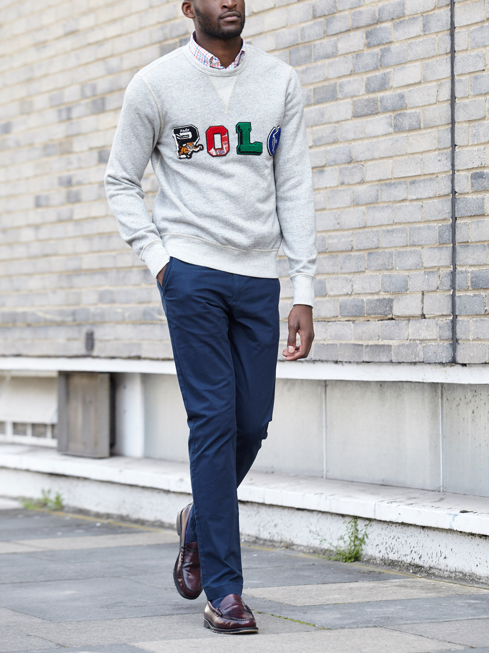 Men's outfit idea for 2021 with logo / printed sweatshirt, micro plaid casual shirt, navy chinos. Suitable for spring and fall.