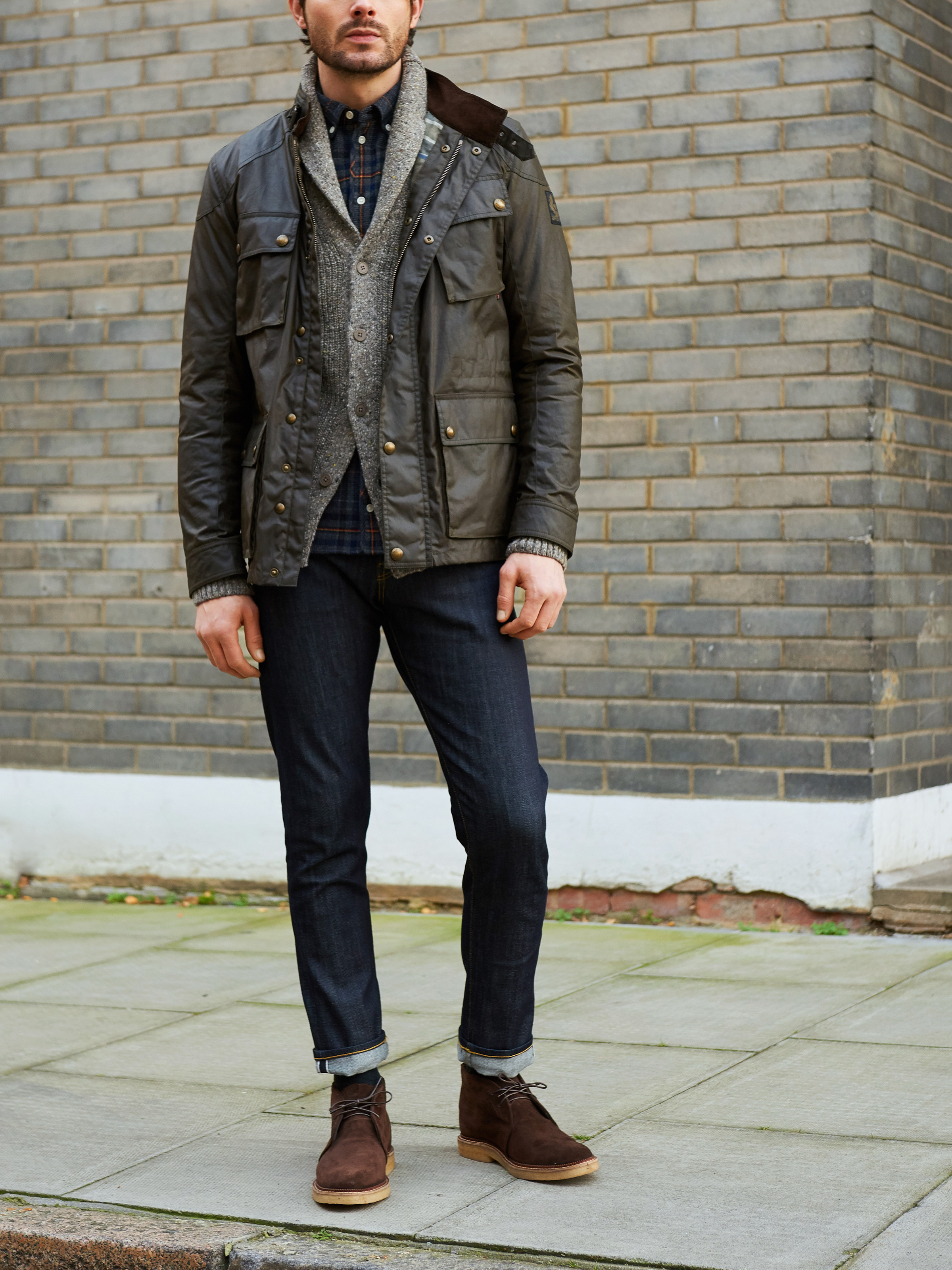 Men's outfit idea for 2021 with field jacket, grey shawl cardigan, bold plaid shirt, dark blue jeans, brown desert boots. Suitable for autumn and winter.