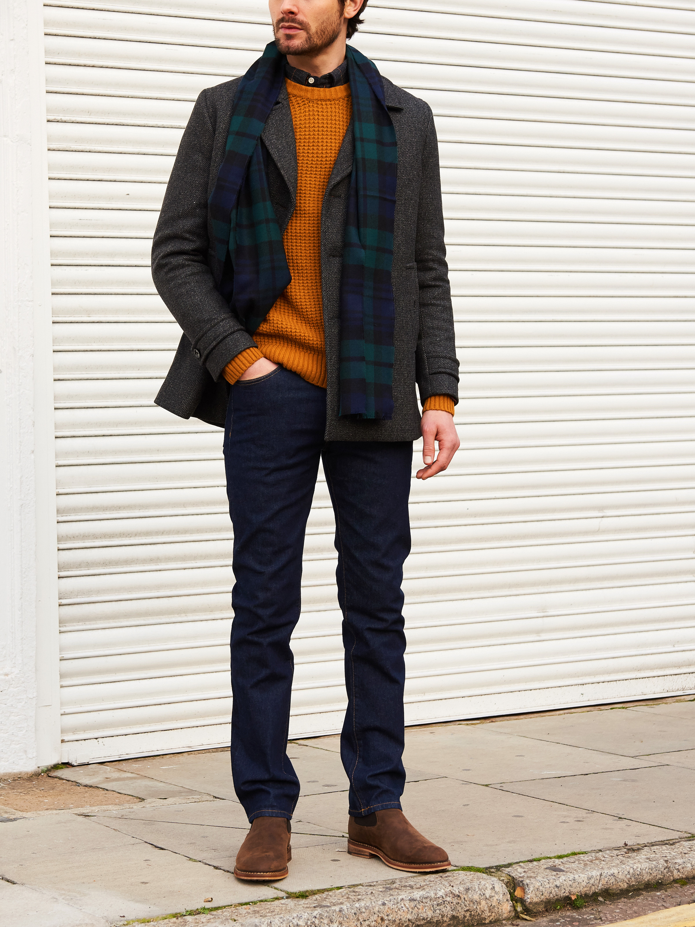 Men's outfit idea for 2021 with single-breasted overcoat, bold coloured crew neck jumper, neutral plaid shirt, dark blue jeans, patterned knitted scarf. Suitable for autumn and winter.