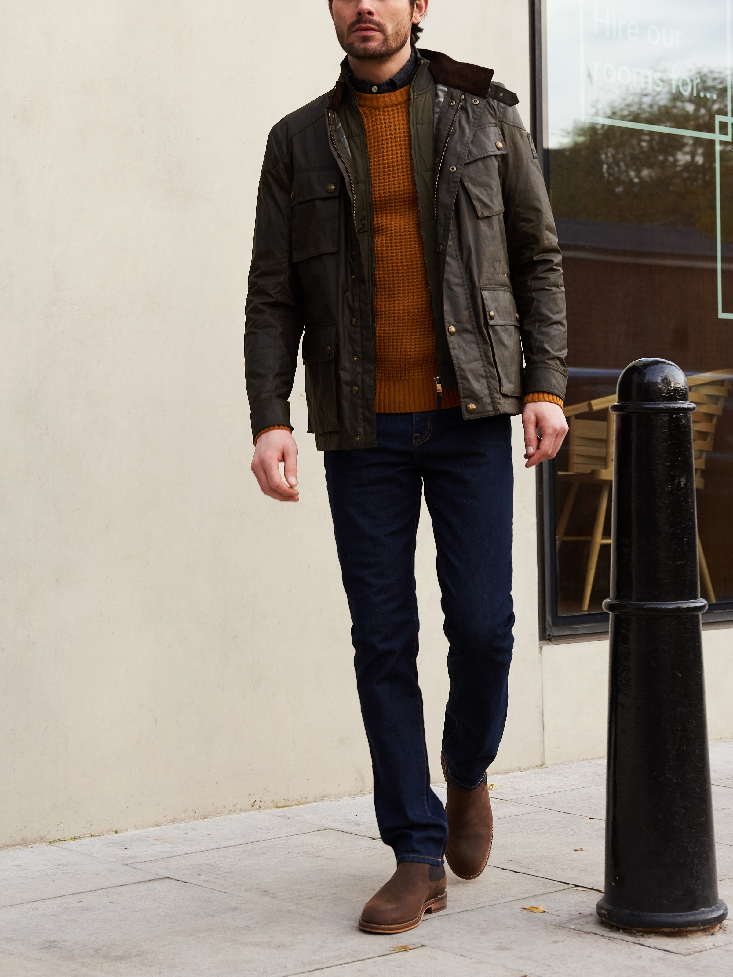 Men's outfit idea for 2021 with field jacket, bold-colored crew neck sweater, neutral plaid shirt, dark blue jeans, brown chelsea boots. Suitable for fall and winter.