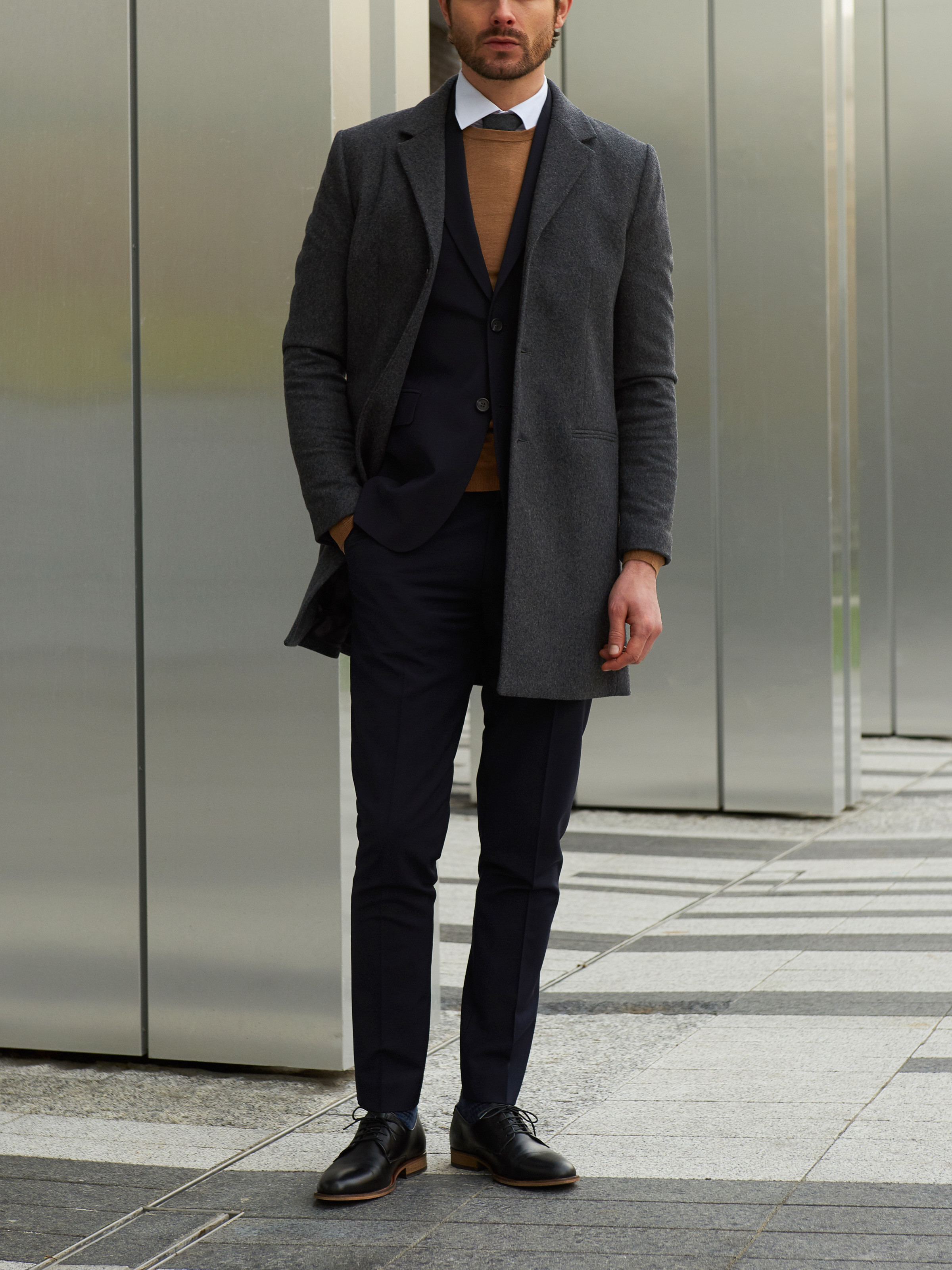 Men's outfit idea for 2021 with single-breasted overcoat, pale-colored crew neck sweater, white dress shirt, navy dress pants, oxford / derby shoes. Suitable for fall and winter.