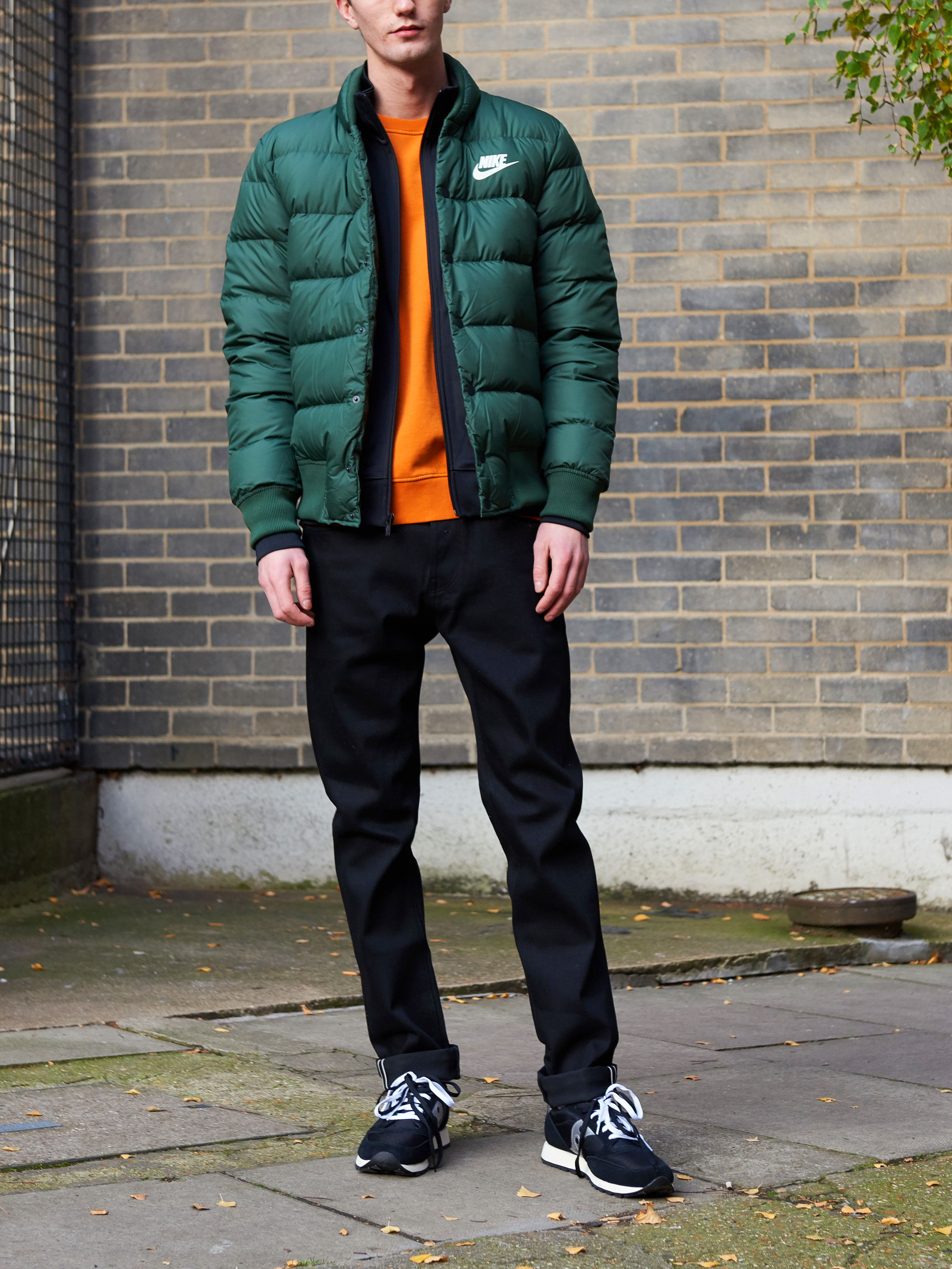 Men's outfit idea for 2021 with quilted jacket, navy varsity / track jacket, bold-colored sweatshirt, black jeans, neutral sneakers. Suitable for fall and winter.